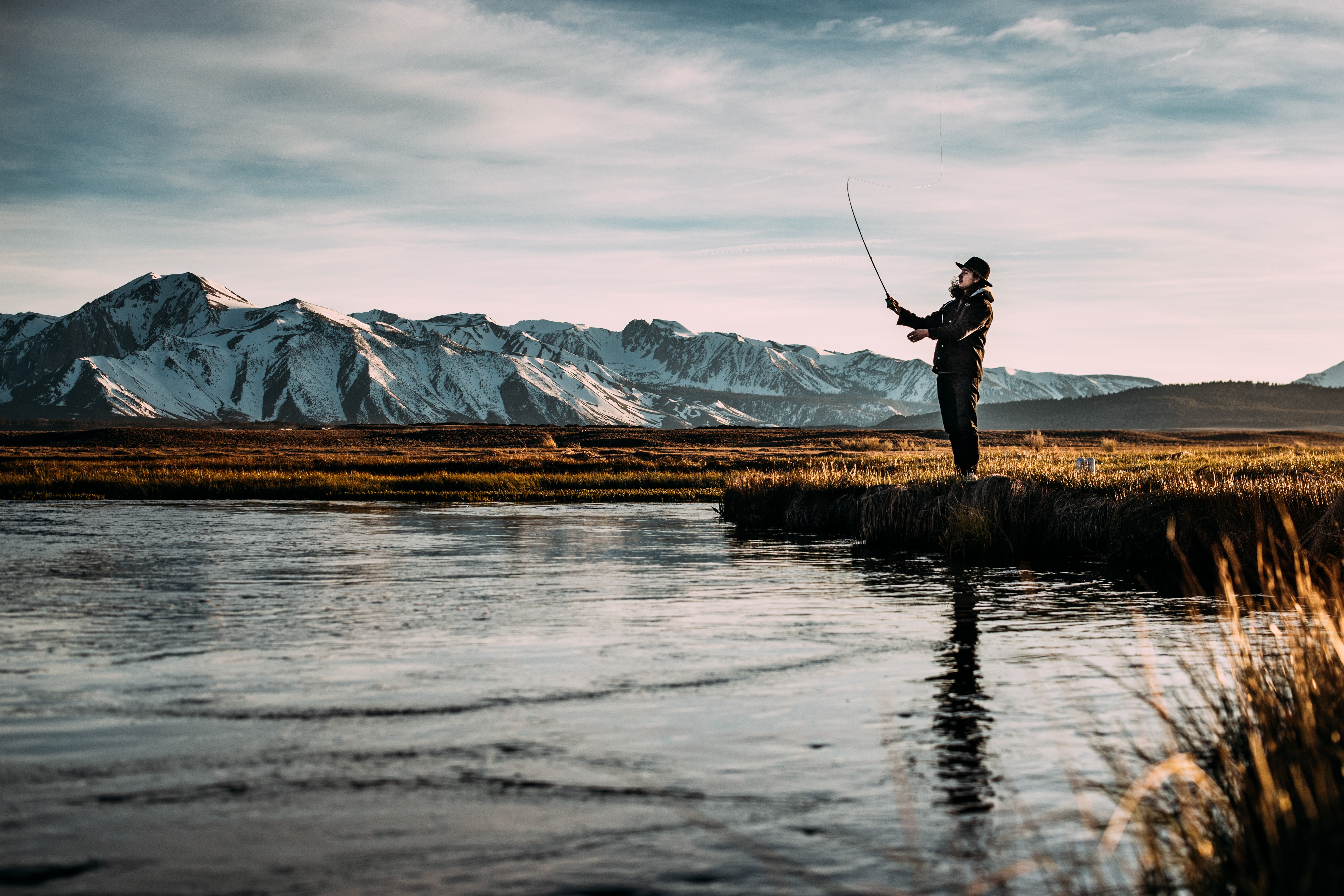 landscape photo of man fishing on river near mountain alps