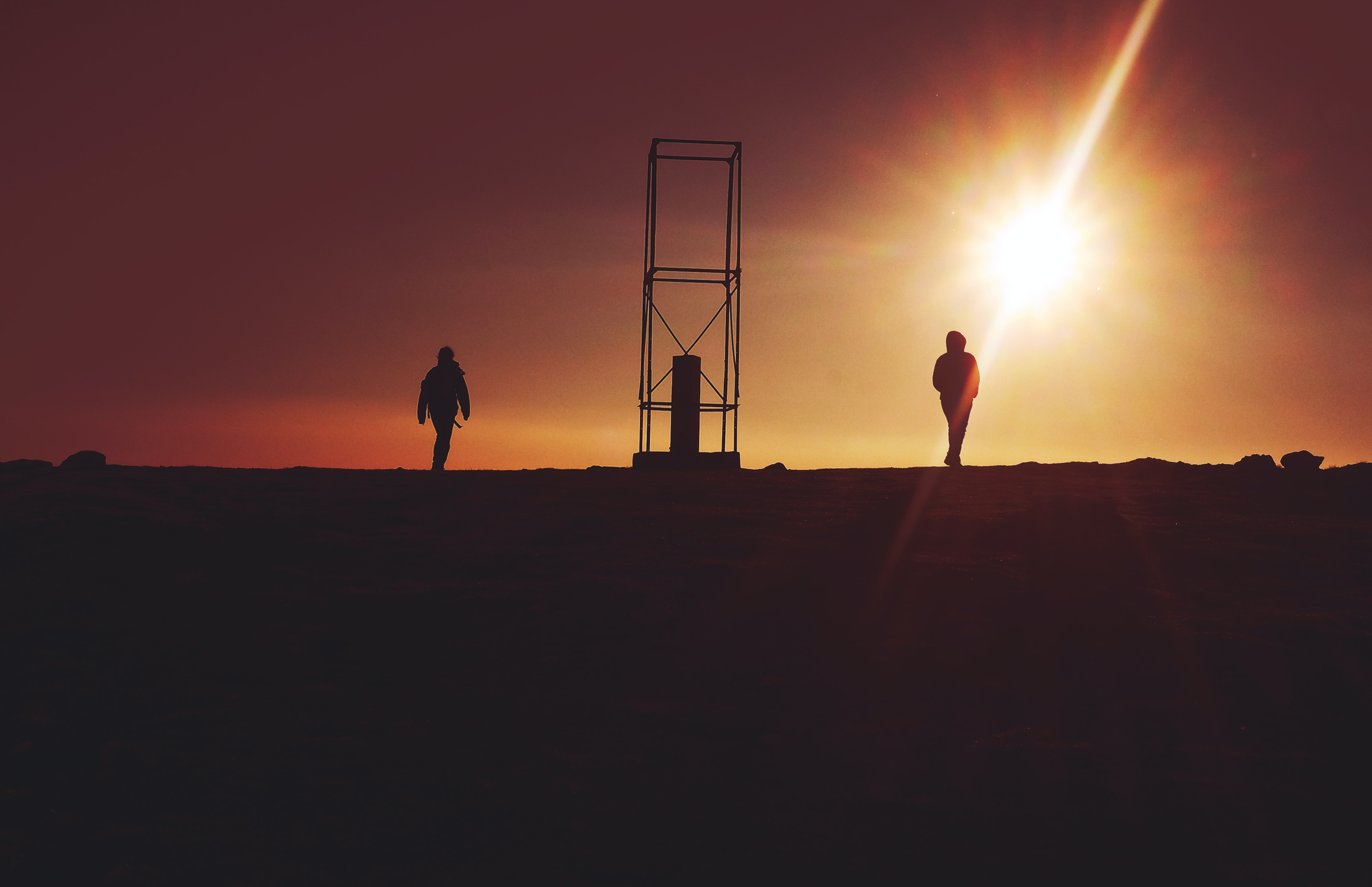 silhouette of two person near gray metal frame during sunet