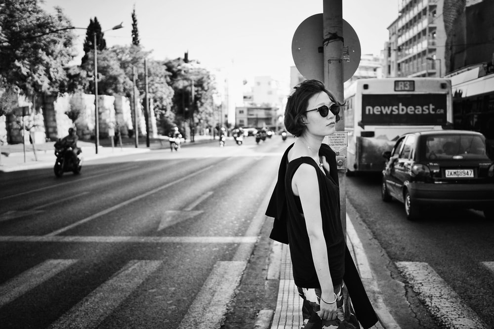 grayscale photo of woman standing beside road signage