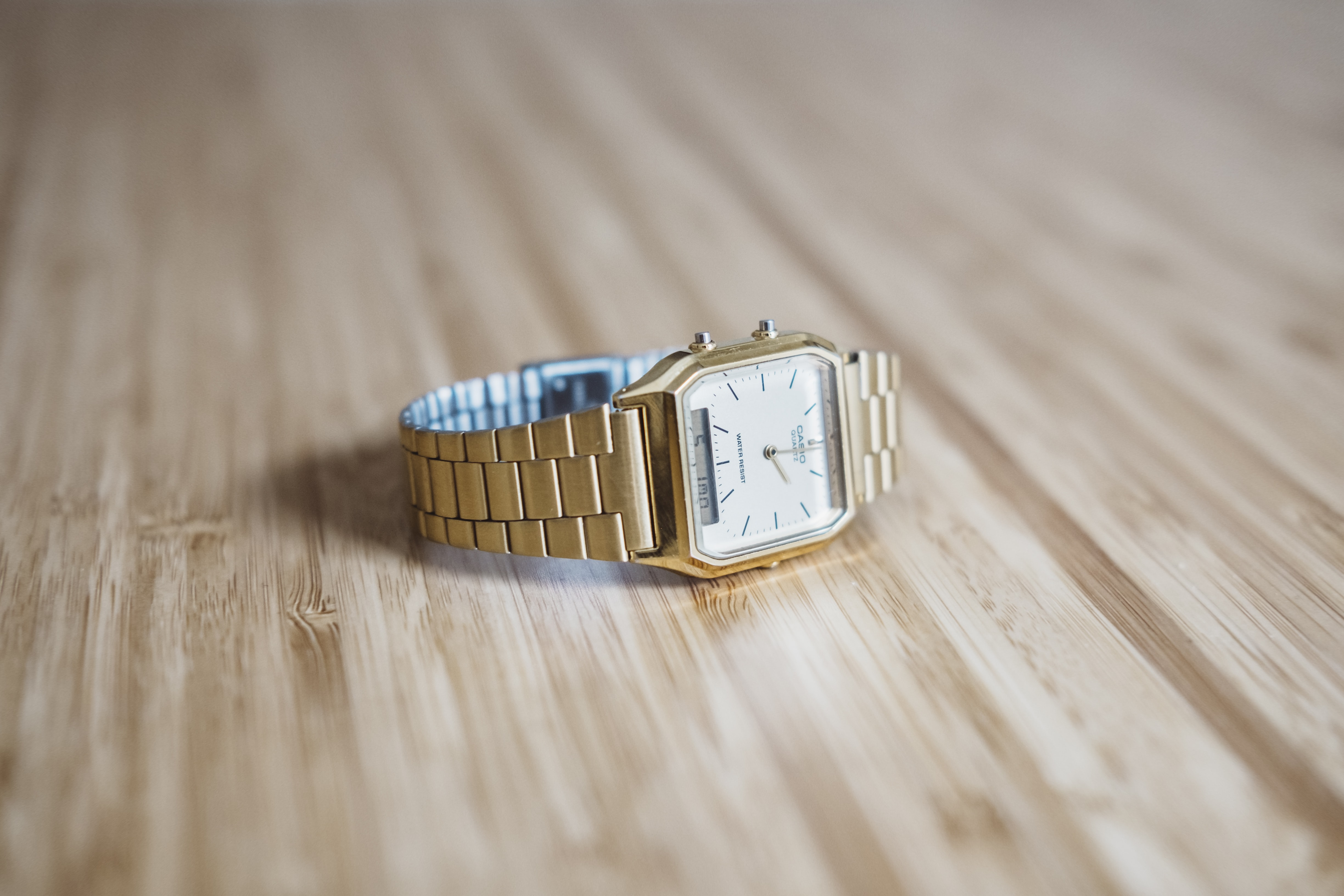A gold Casio watch is placed on a wooden surface in Amersfoort.