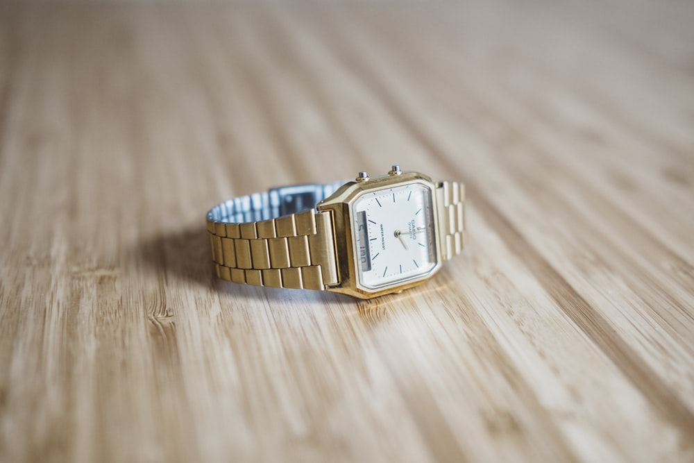 square gold-colored analog watch on brown wooden board