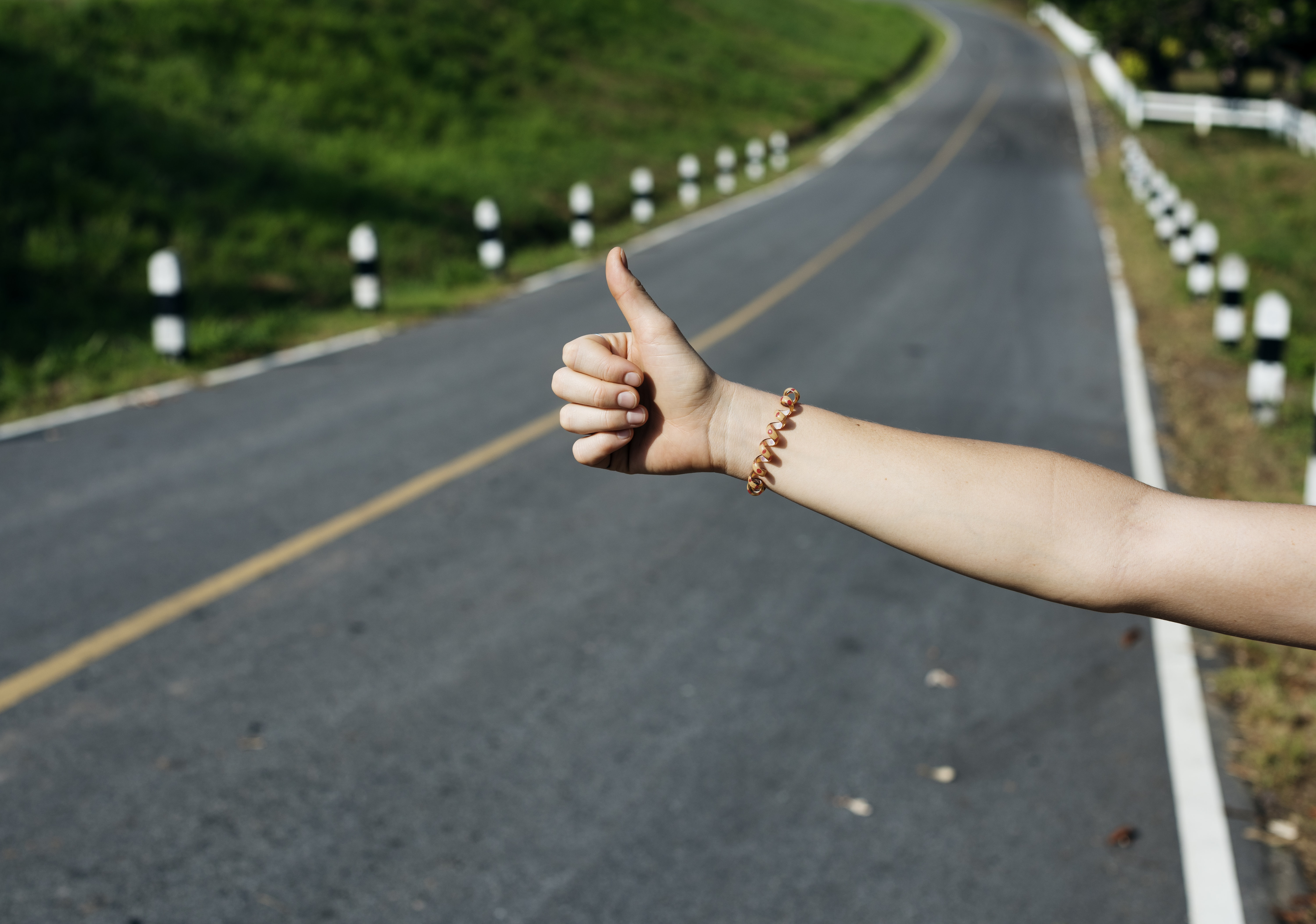 Person's arm with bracelet displaying hitch hiking sign near asphalt road