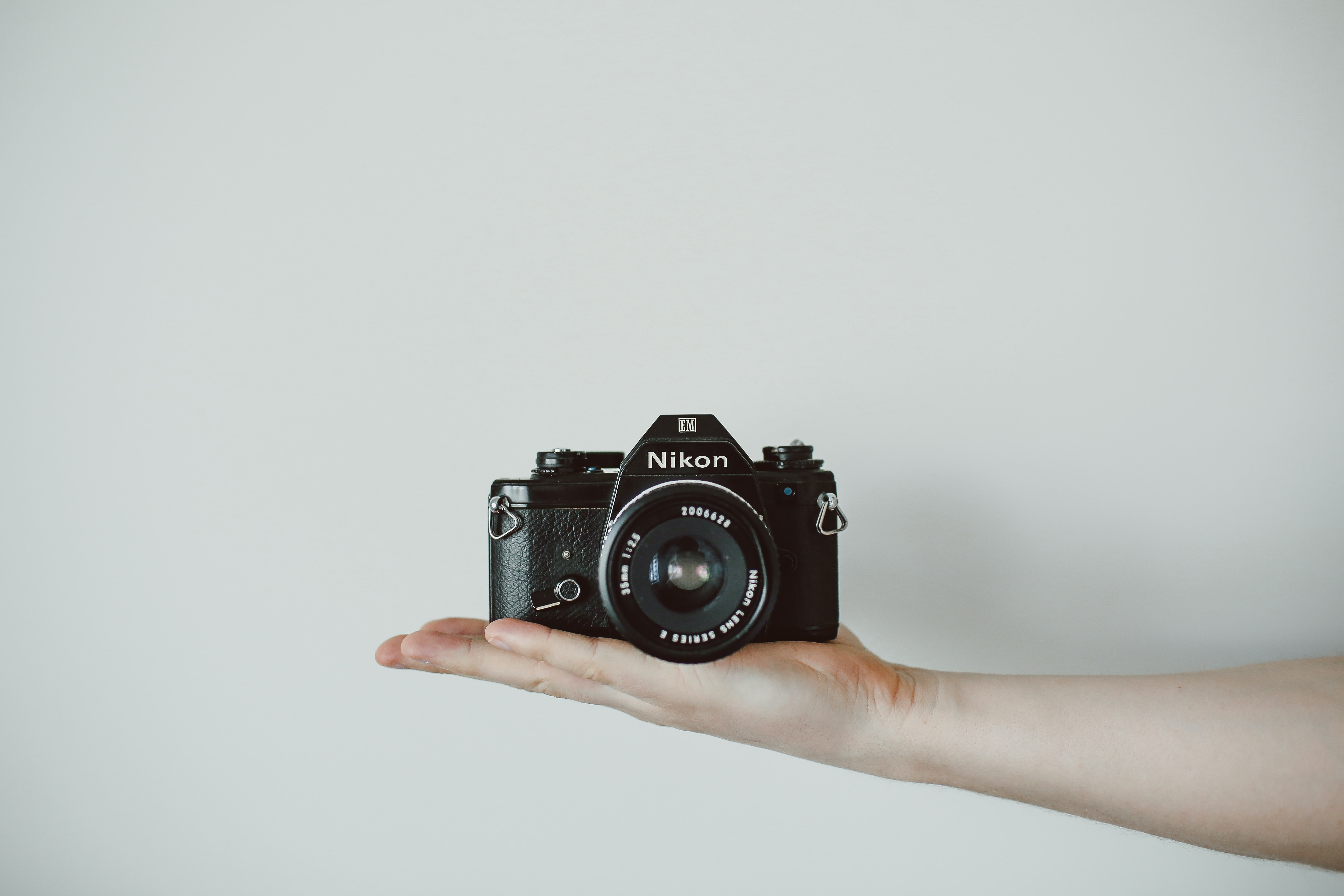 A person holding a Nikon camera in the palm of their hand against a white wall