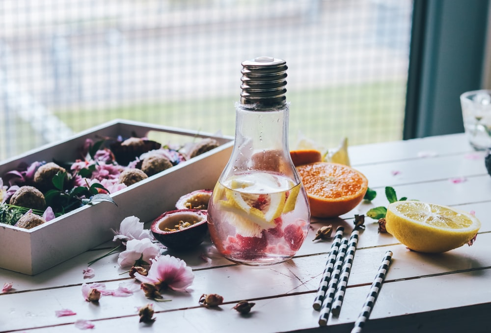 clear glass light bulb pitcher with sliced lemon and orange fruits on top of white table