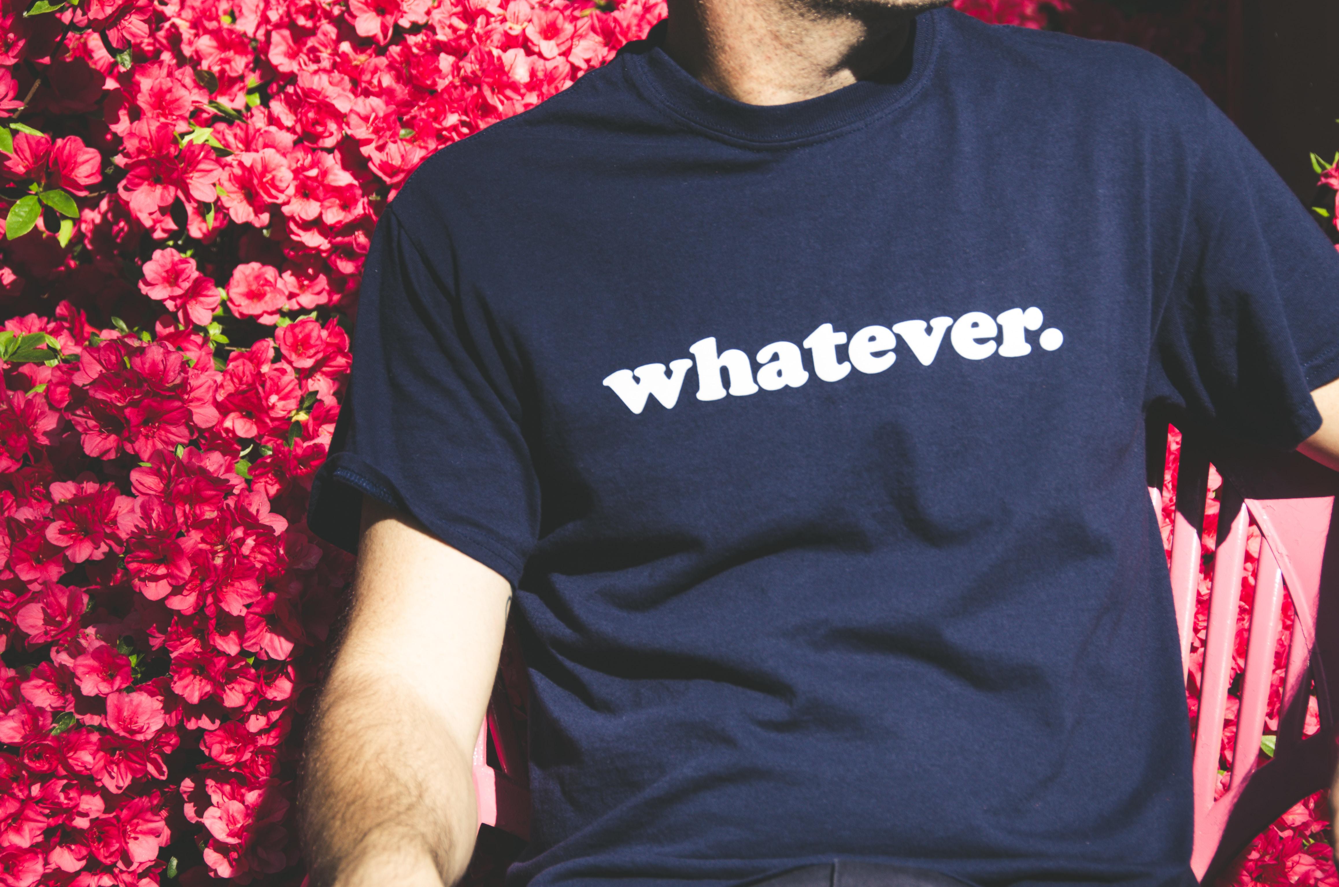 "A man in a ""whatever."" shirt sitting near a pink flower bush"