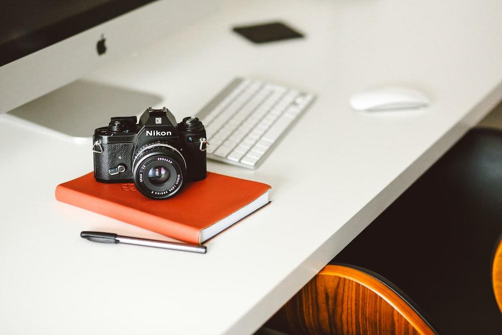 black Nikon DSLR camera on red notepad