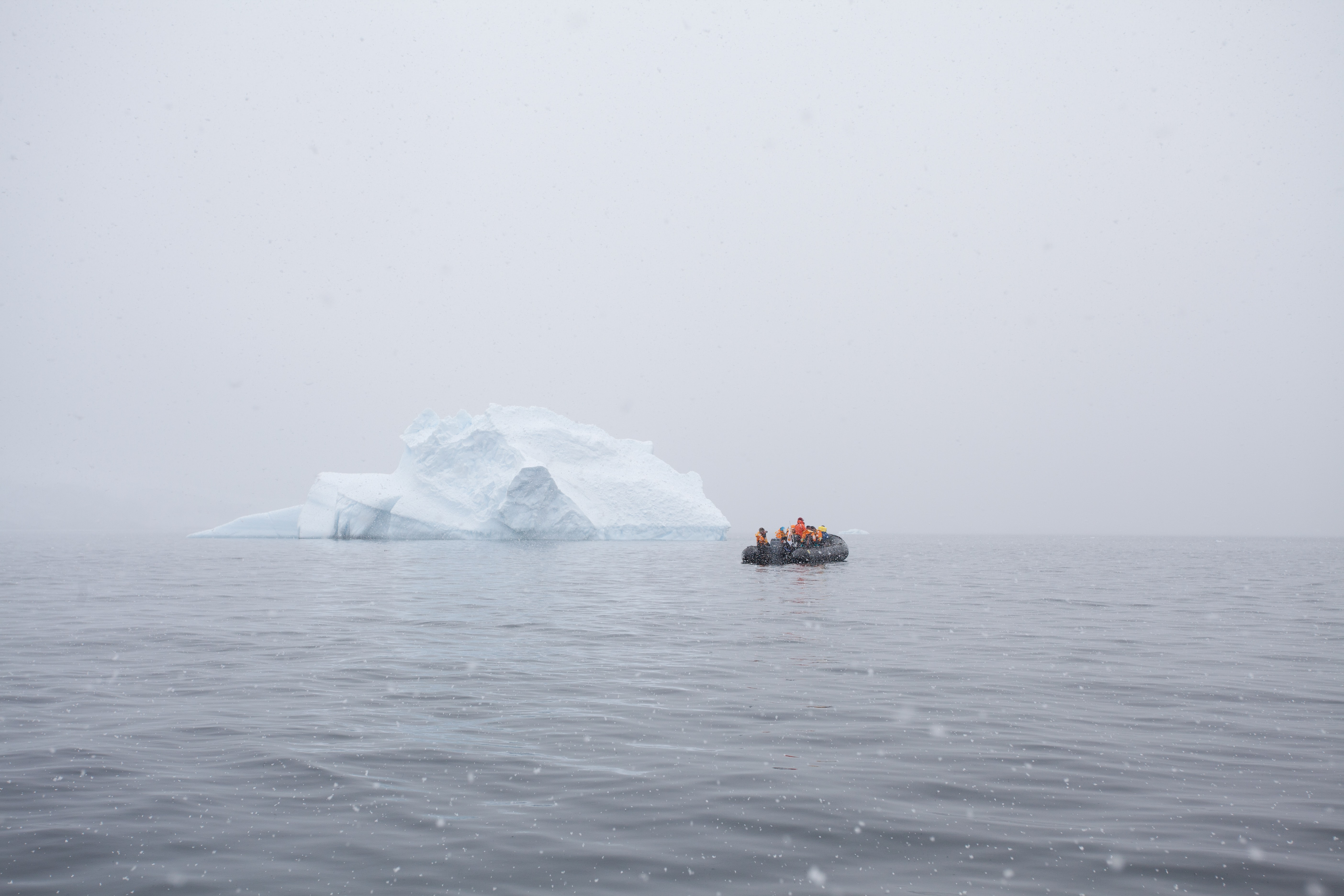 A group of people in a raft in the middle of the ocean next to a small iceberg with fog surrounding the area.