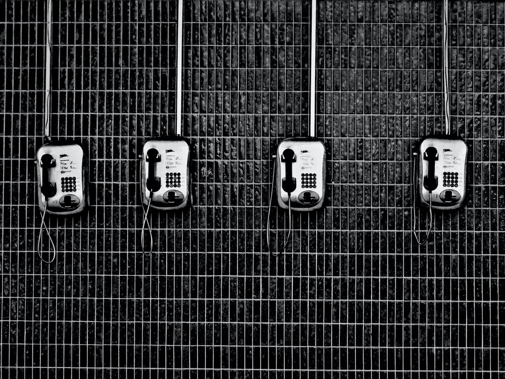 Black and white shot of four payphones on dark tiled wall
