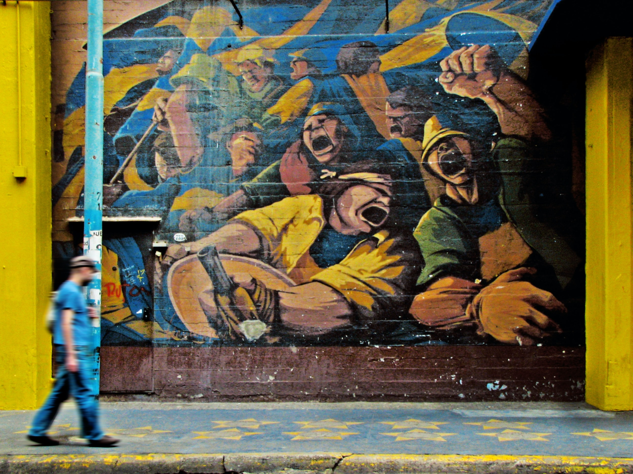 Man walking on sidewalk with lamppost in front of graffiti of passionate workers, La Boca