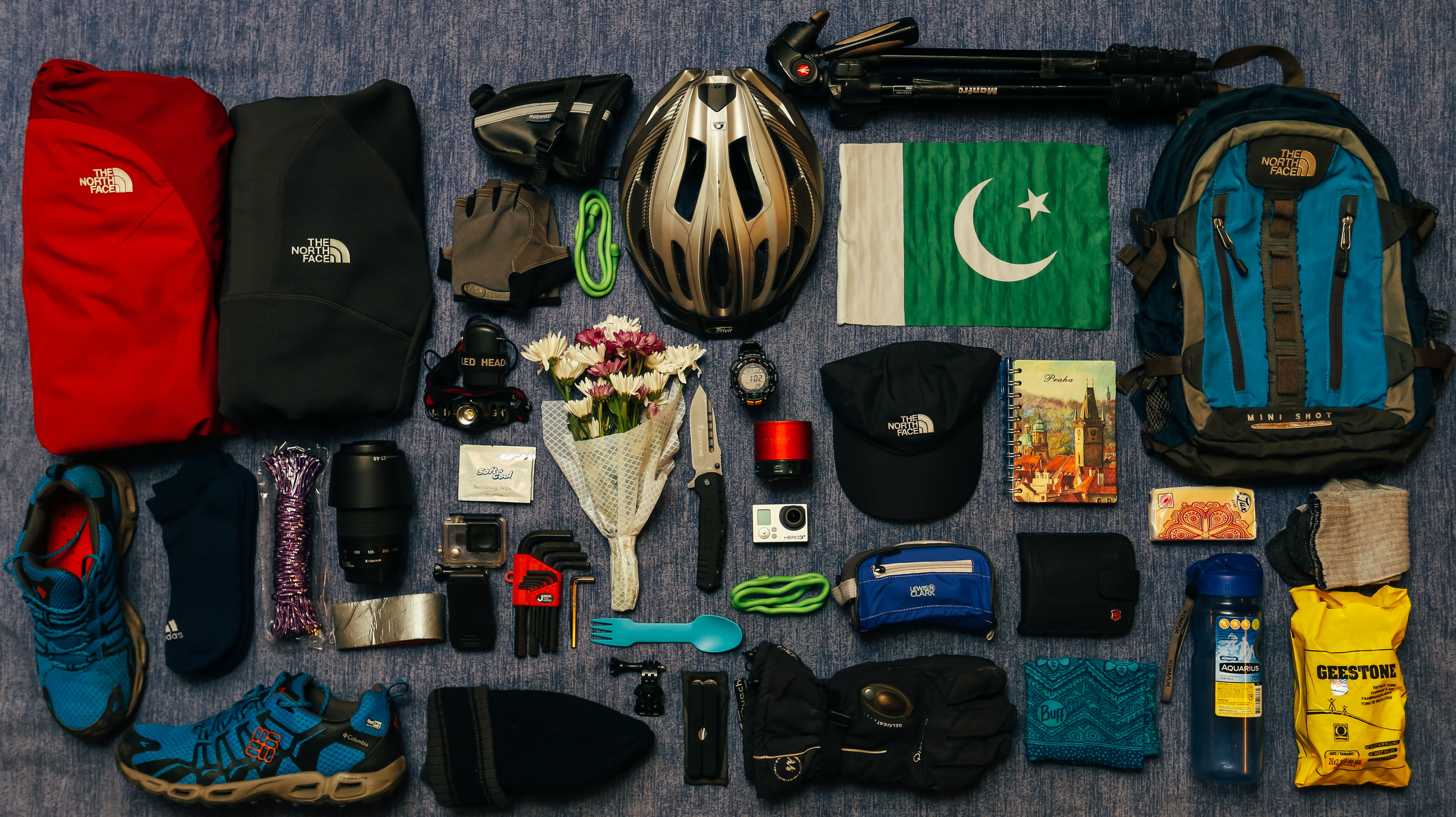 Biking and camping equipment, flowers, and flag sit neatly on blue surface