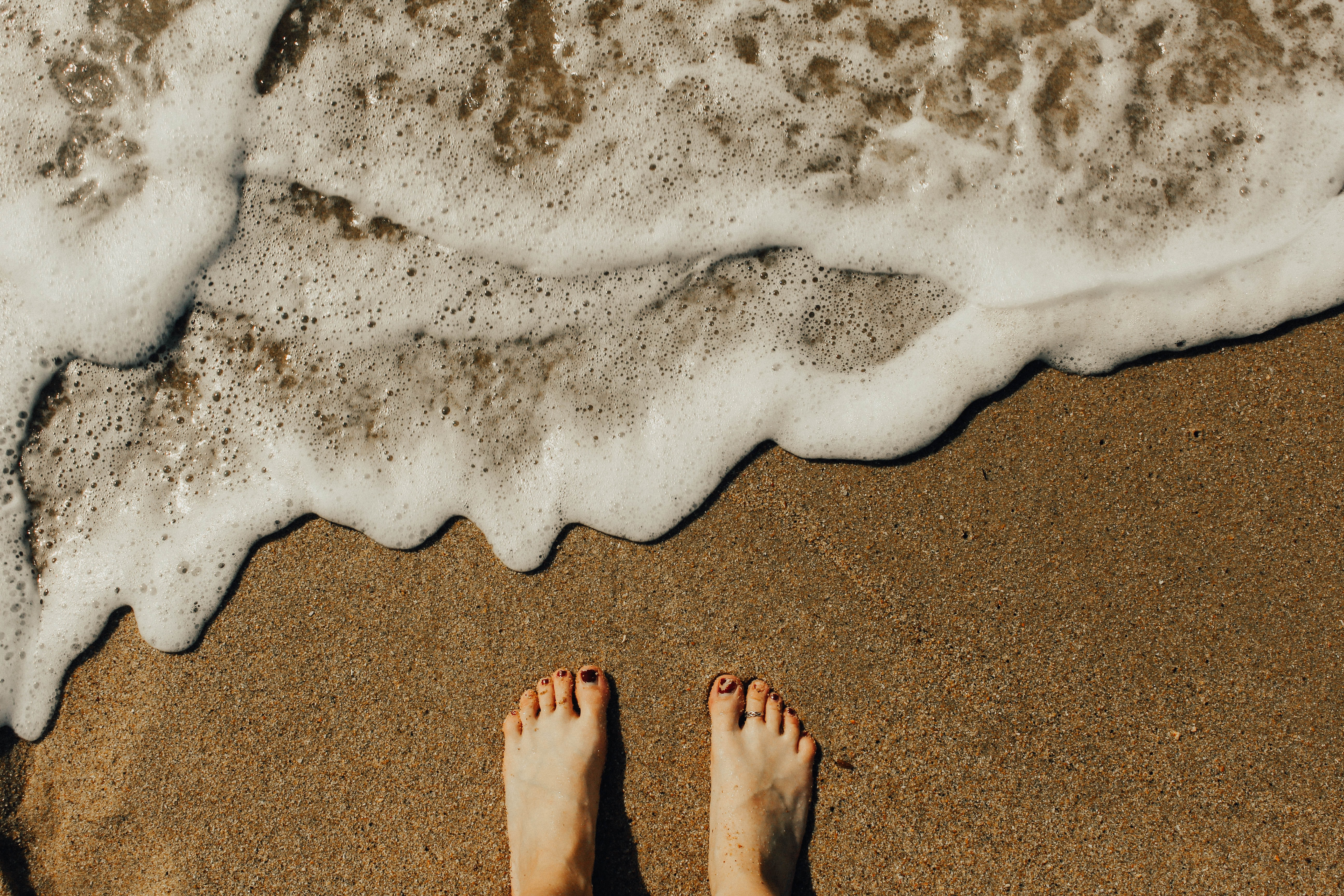 An overhead shot of a person's feet in wet coarse sand next to small foaming waves