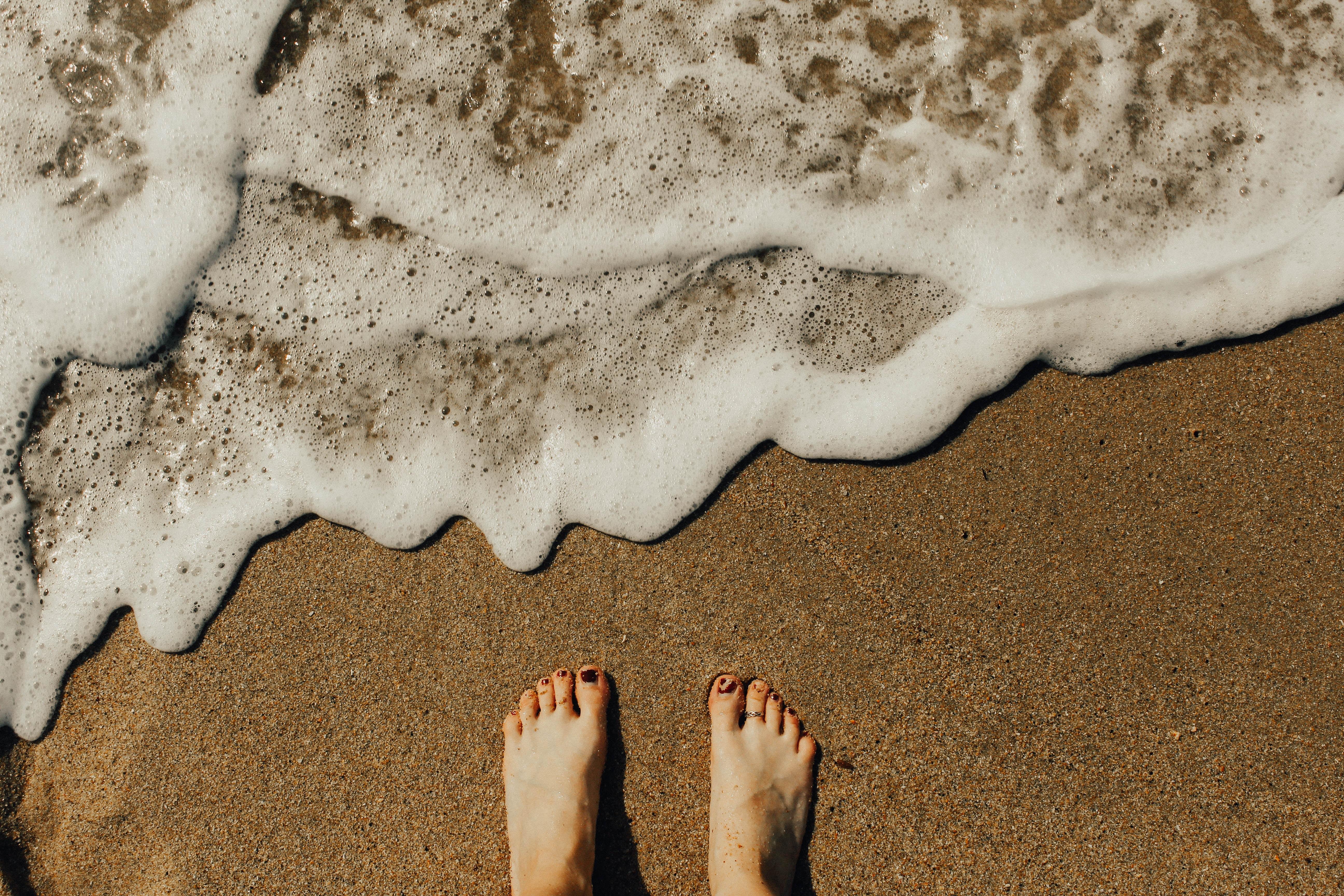 person's feet on seashore