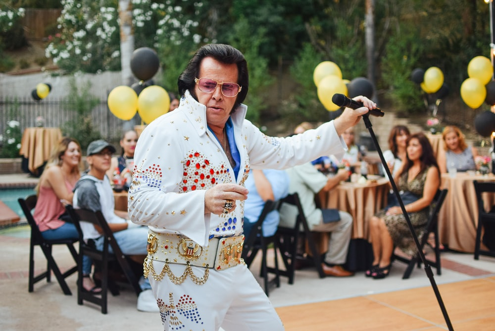 Elvis Presley impersonator awkwardly sings and dances for a party