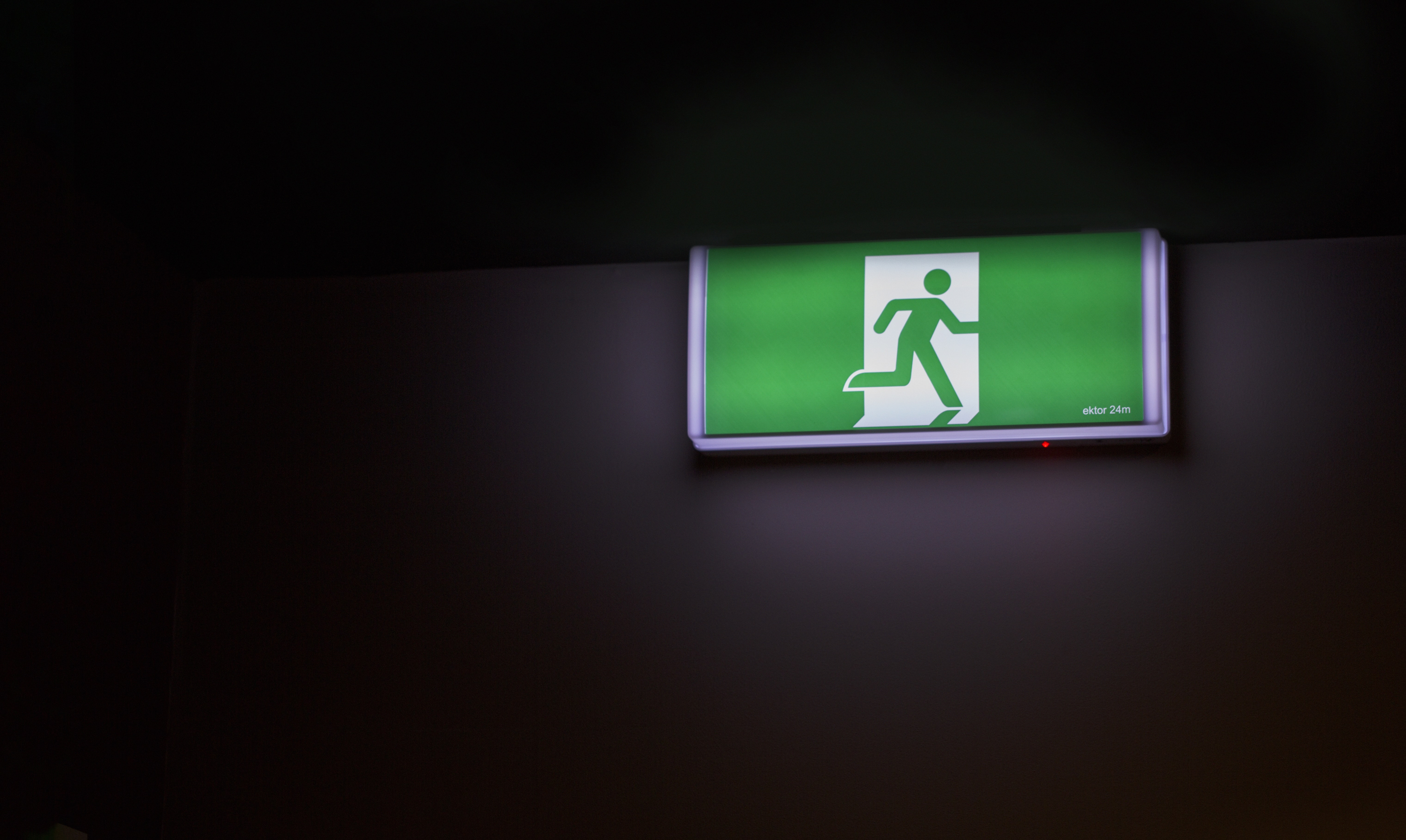 Green exit sign with figure of a person exiting through a door against a black background