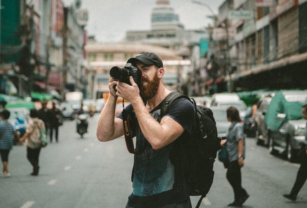 shallow focus photography of man using a DSLR camera