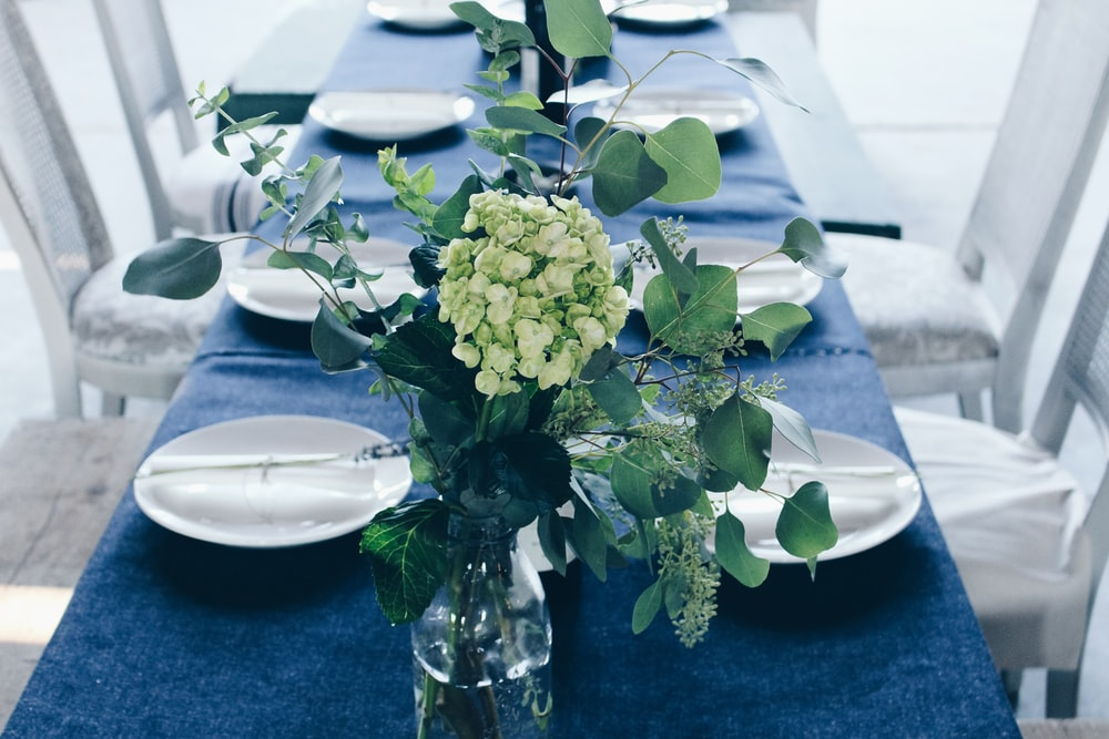 green and white flower centerpiece on table