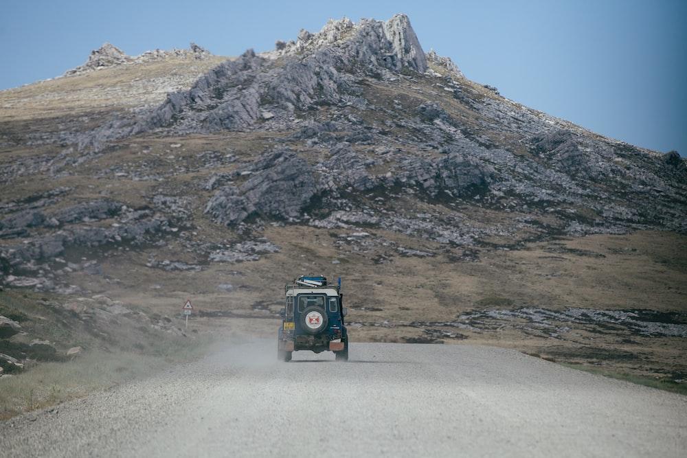 green Jeep on grey asphalt road