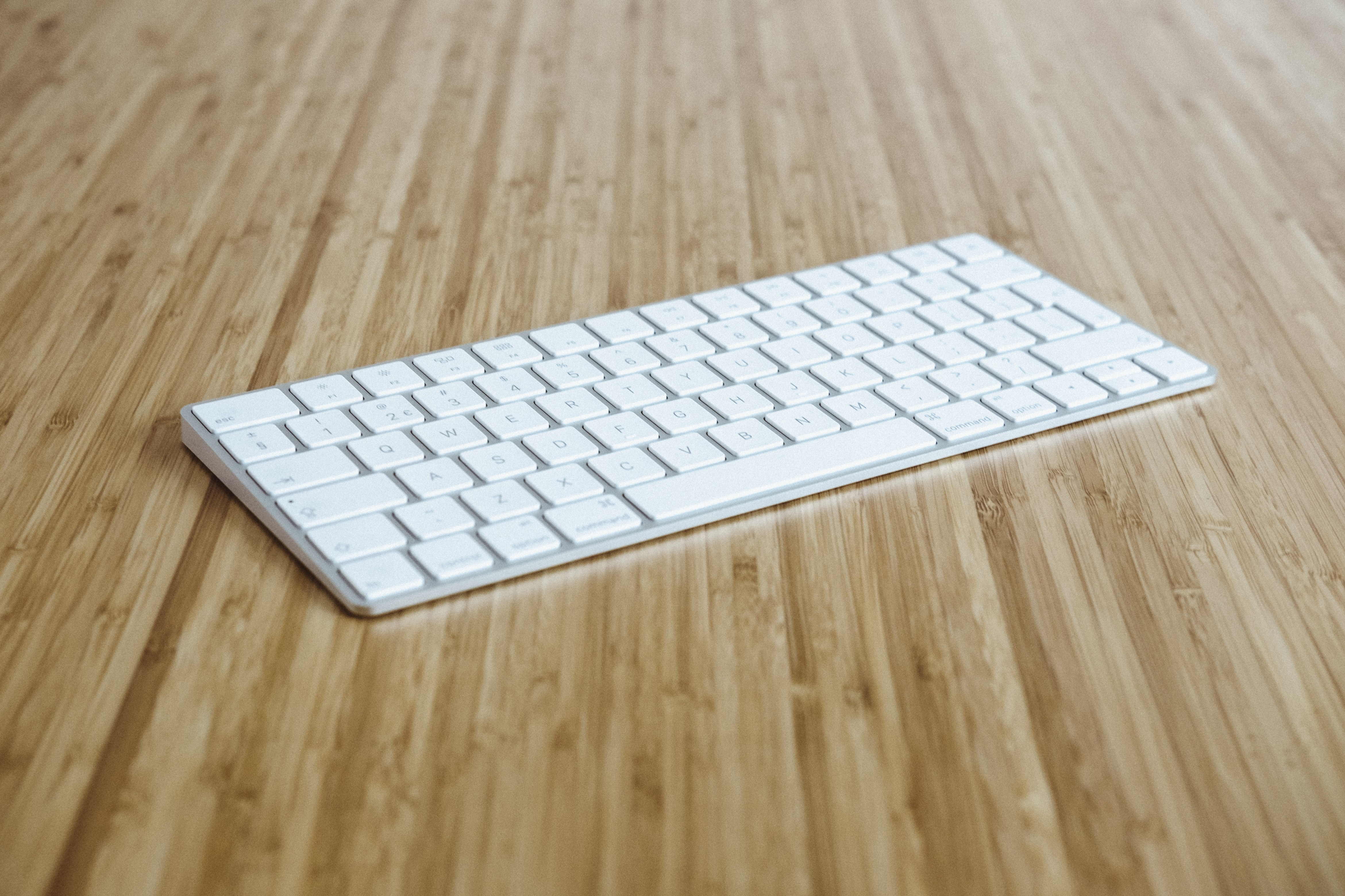 silver and white keyboard on brown wooden surface