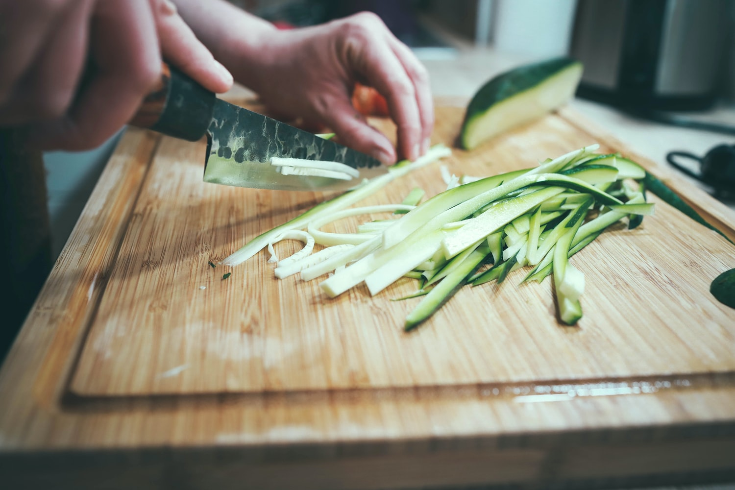 A person is slicing a cucumber