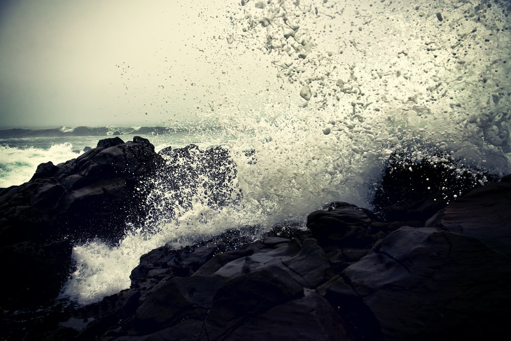 grayscale photography of ocean waves crashing on rock during daytime