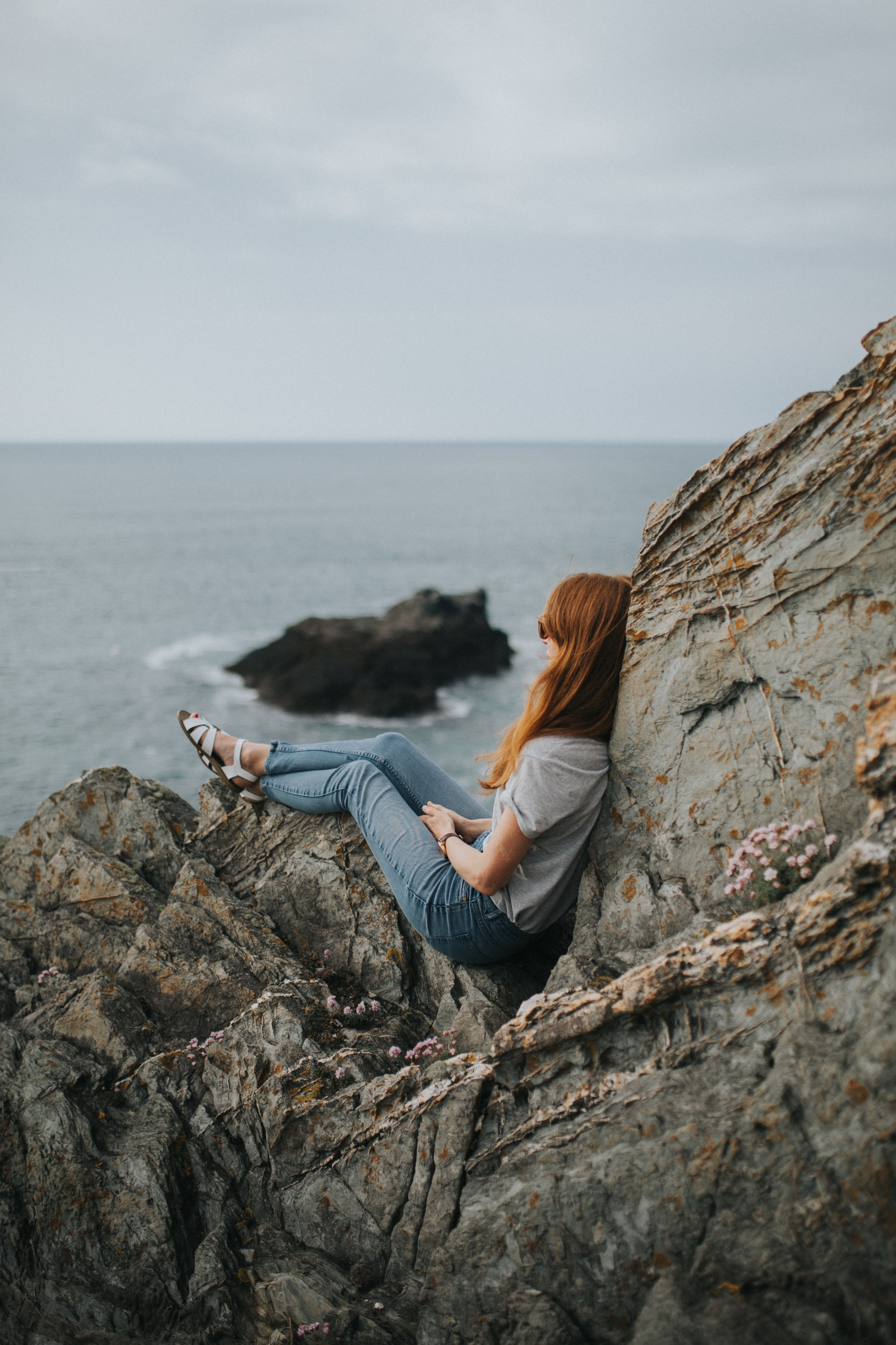 Woman in jeans and shirt sitting on coastline rocks at Fistral Beach