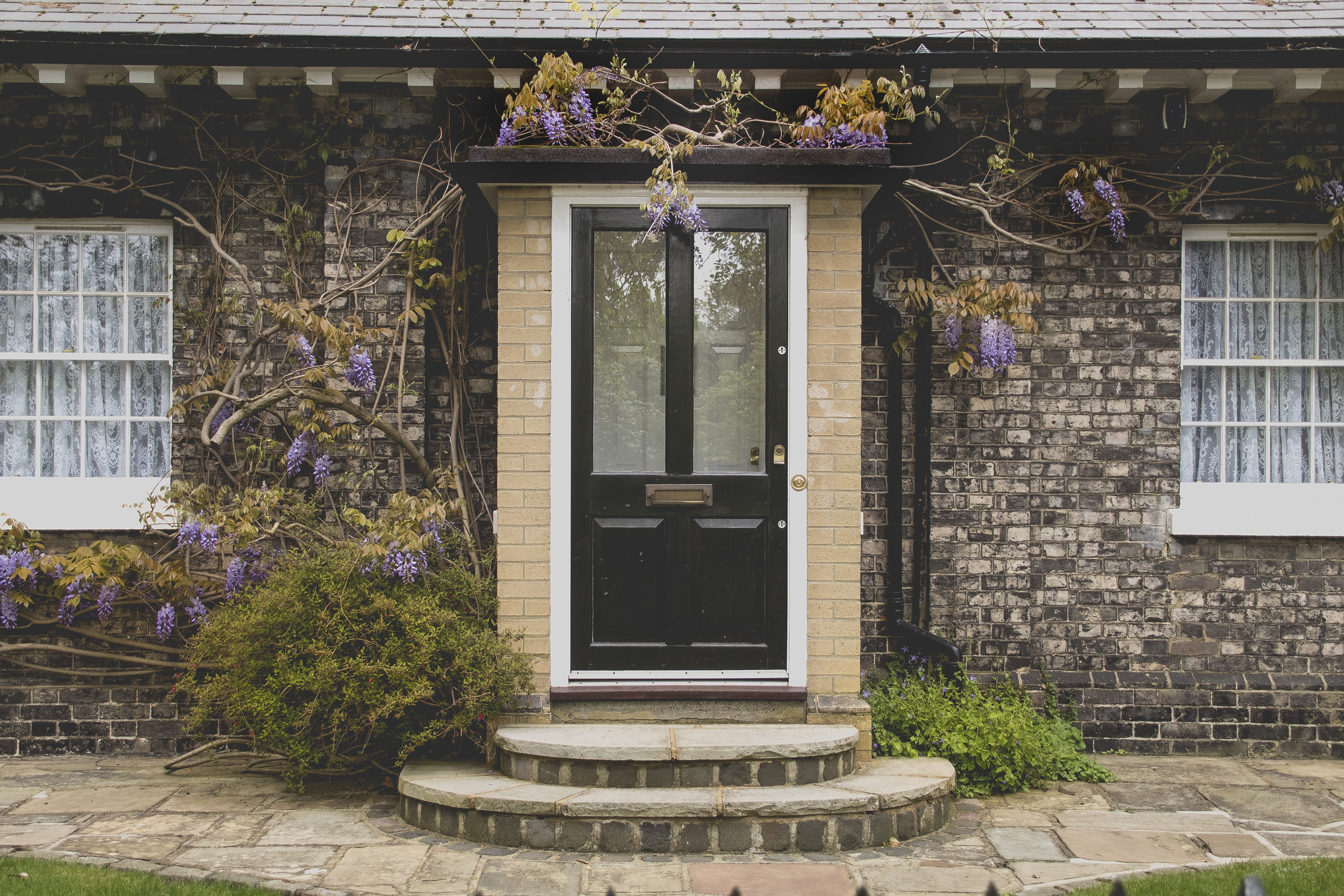 The front door to a house with a flowering bush climbing on the porch