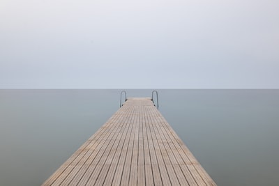brown wooden dock with cloudy sky minimalist zoom background