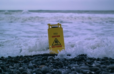 caution wet floor signage on gray rocks in seashore