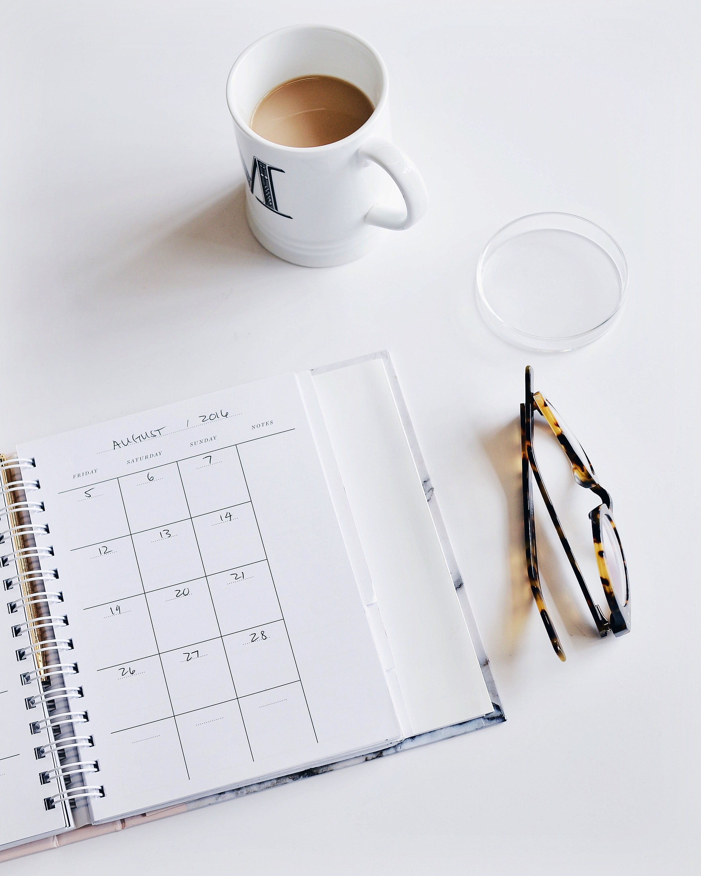 A calendar book, pair of glasses and cup of coffee on a white surface.