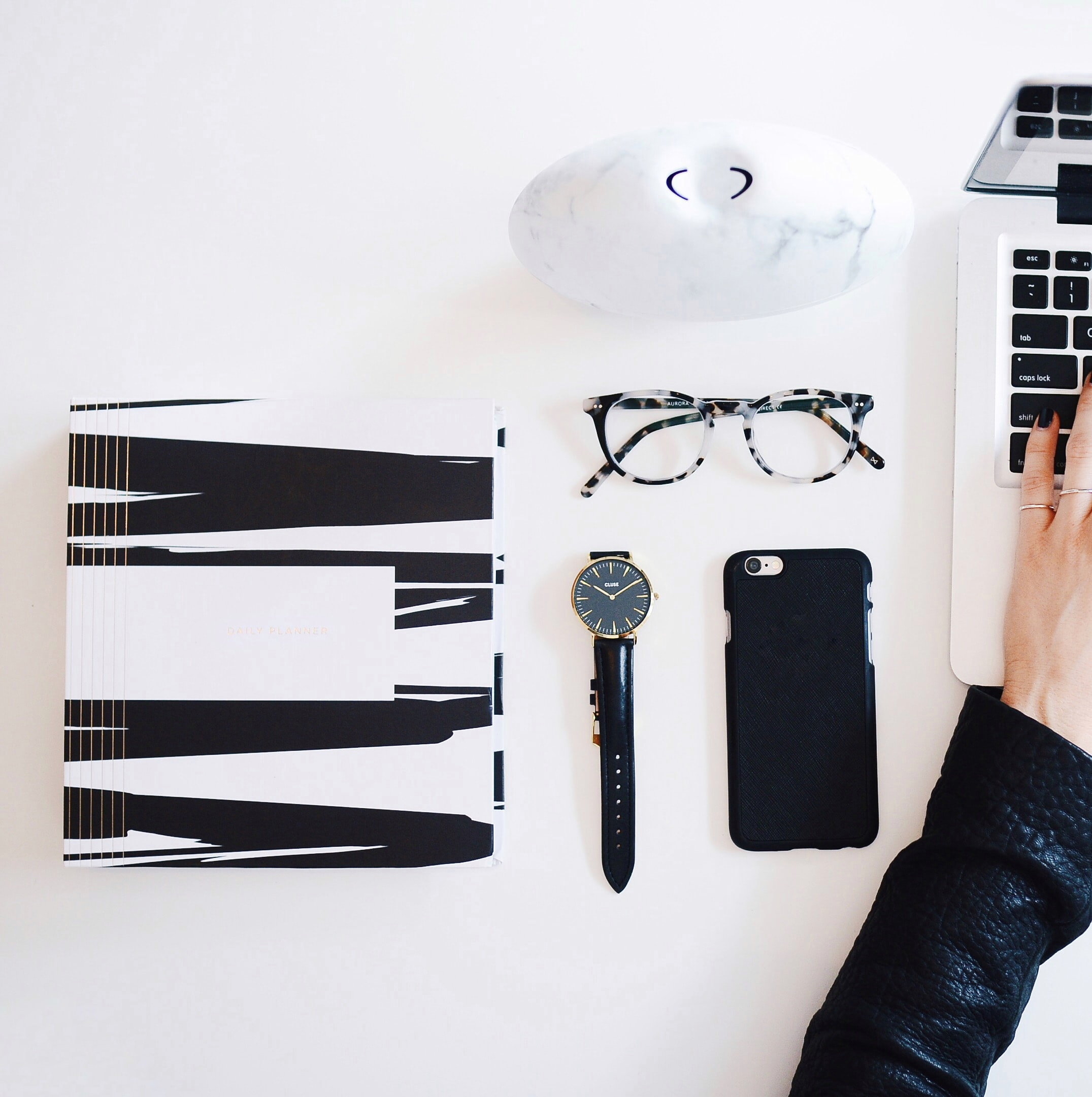 A flatlay image of a white desk with a laptop, reading glasses, a watch, smartphone and various other items.