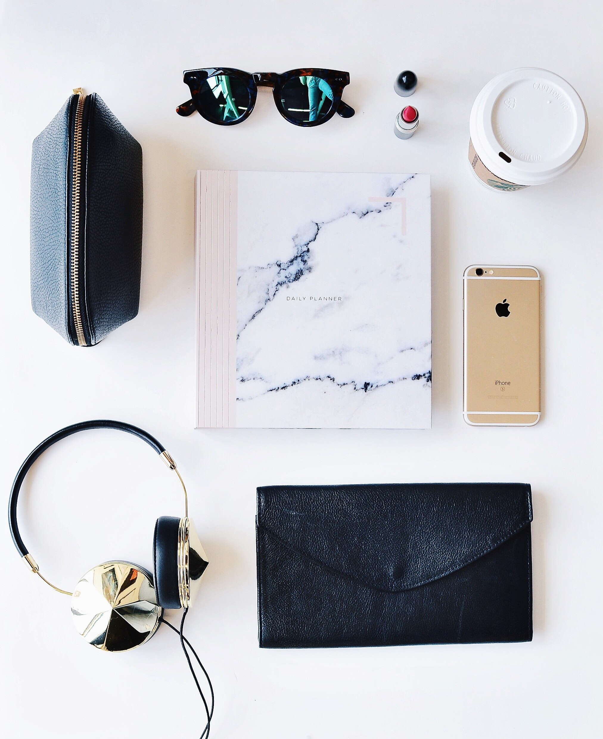 A flatlay image of paper, a smartphone, cup of coffee, glasses and various other items.