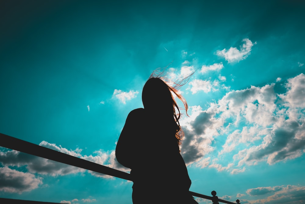 silhouette of woman standing with cloudy sky