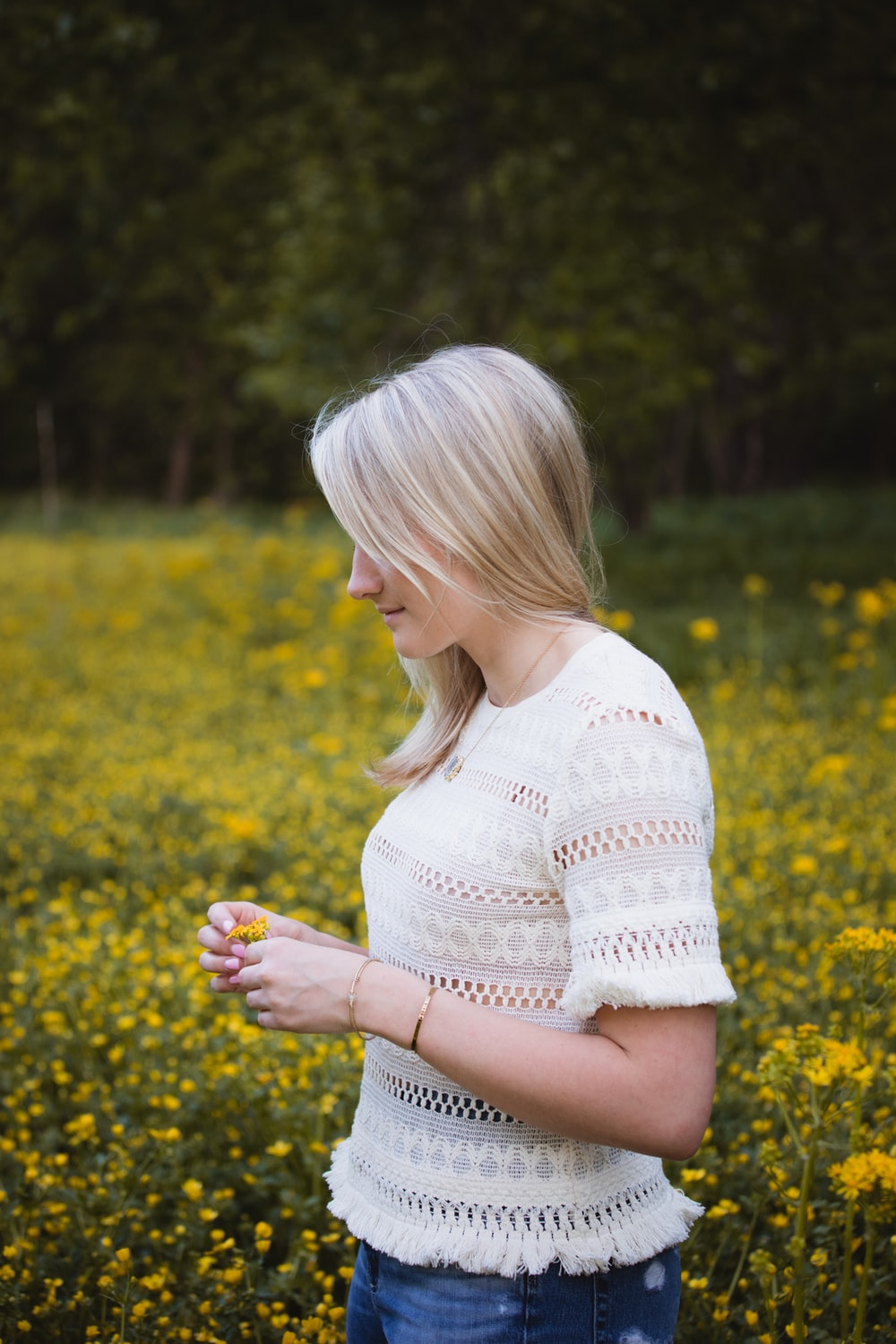 woman wearing white blouse standing and holding yellow flower surrounded with flowers