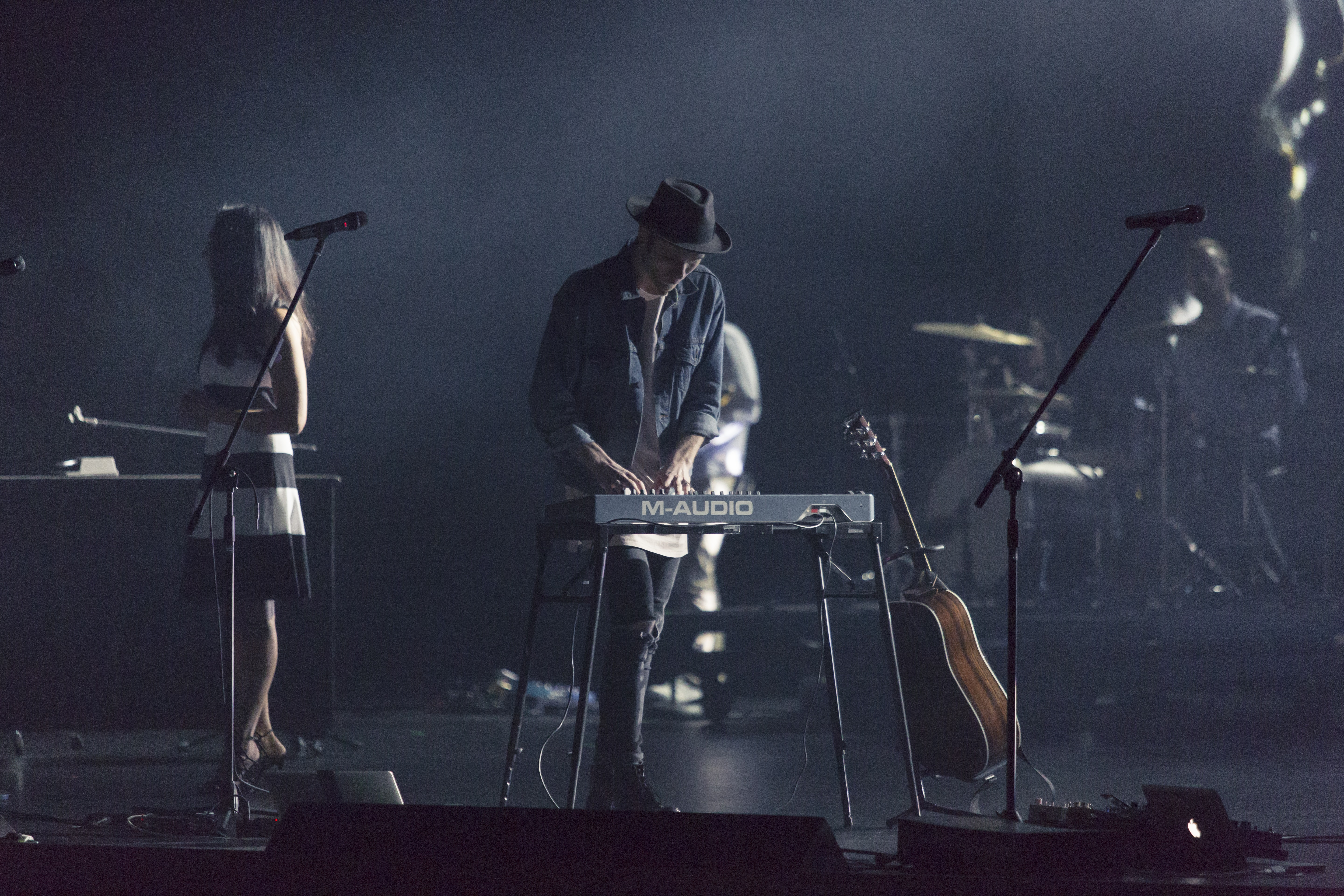 A man in a hat playing the keyboard during a concert with other band members at the back