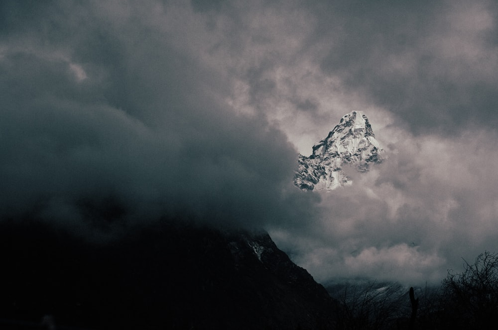 snow covered mountain with clouds