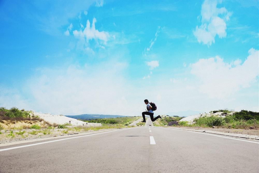 man jumping on street during daytime
