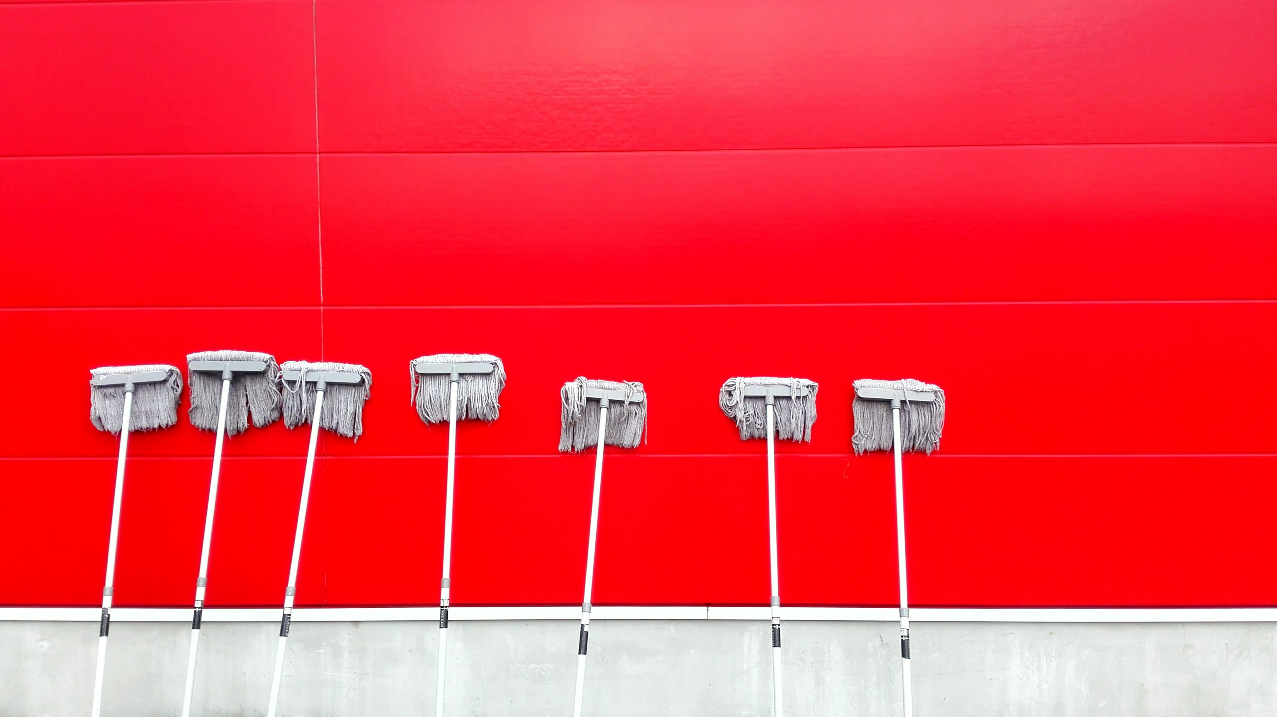 Seven upright mops stand against a red wall
