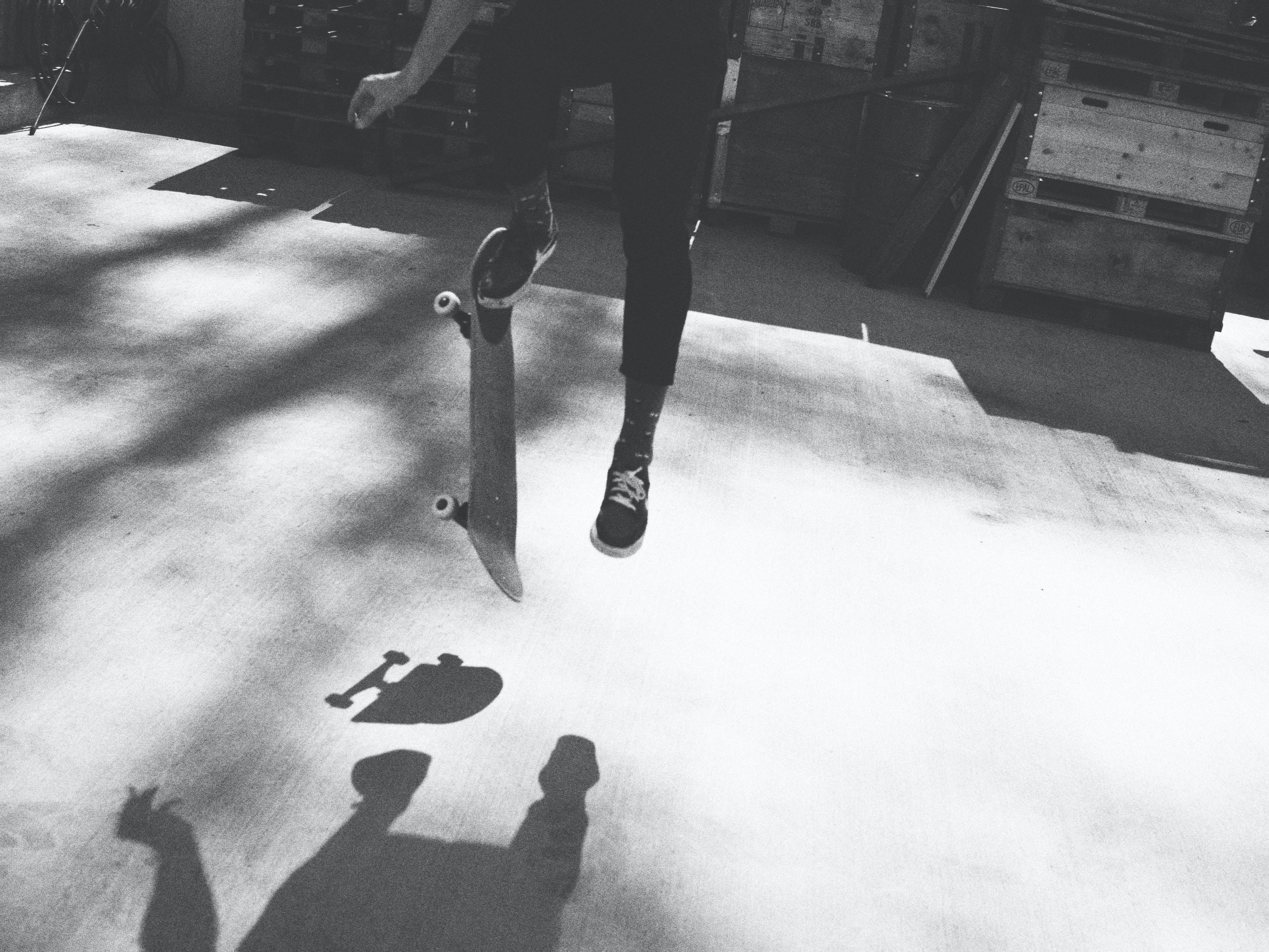 grayscale photography of person doing skateboard tricks
