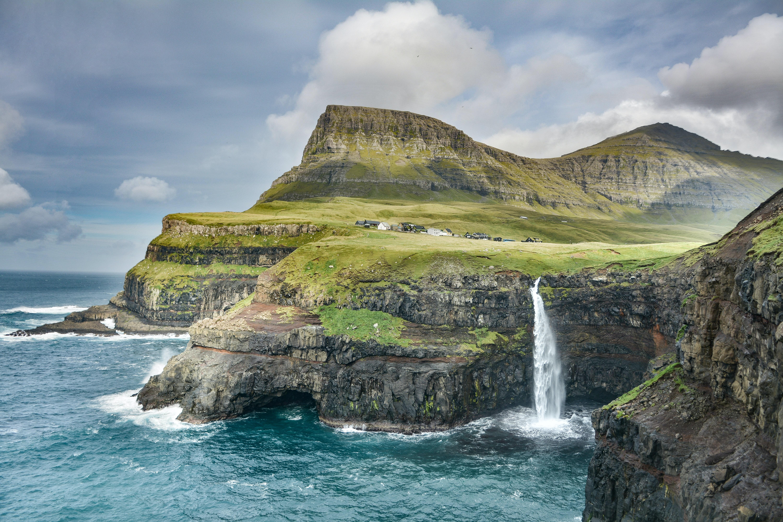 waterfalls on mountain under nimbus clouds