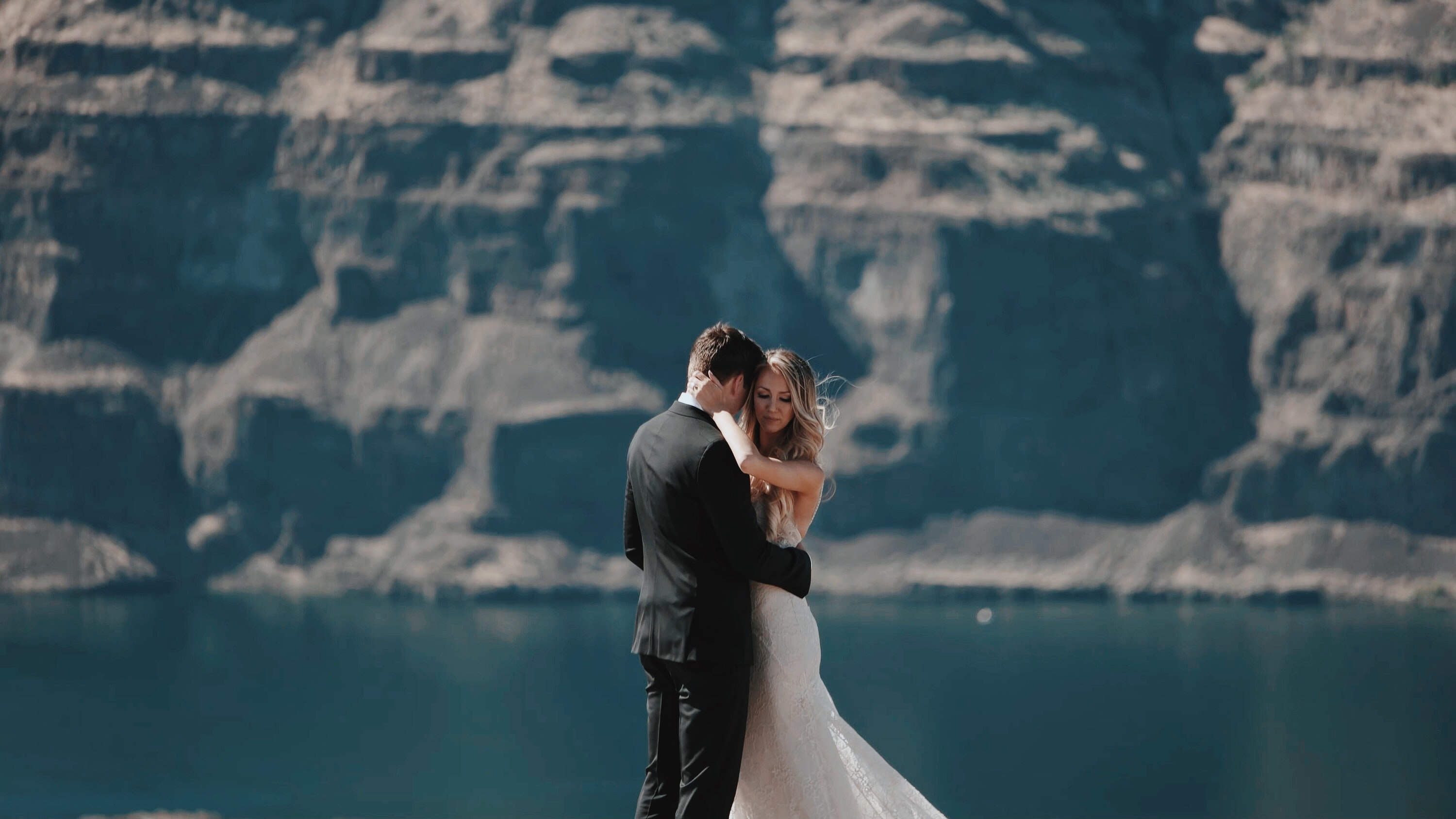A bride and groom embrace on a vista overlooking a body of water and cliff