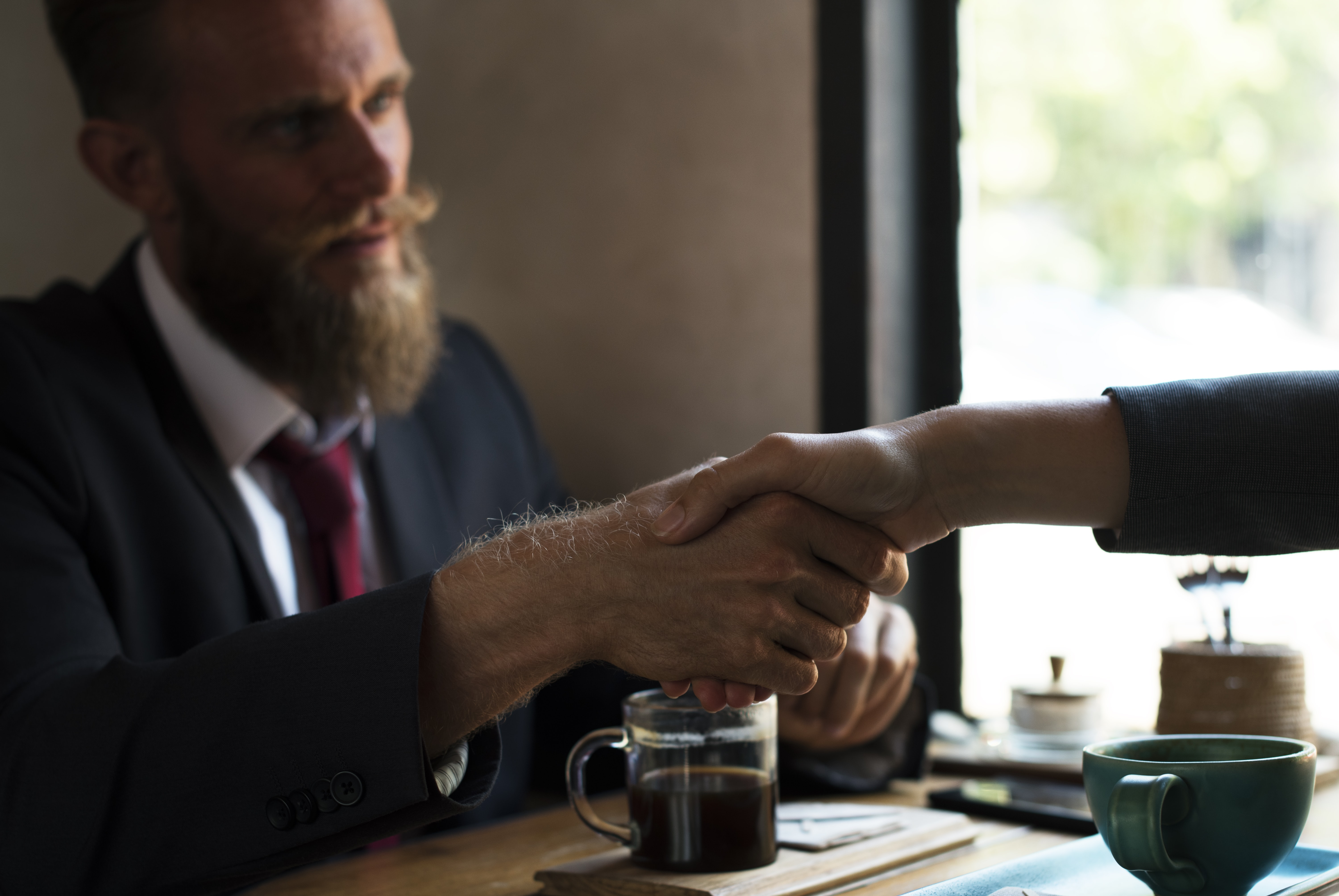 A bearded man having dinner with another person, shaking hands over the table.