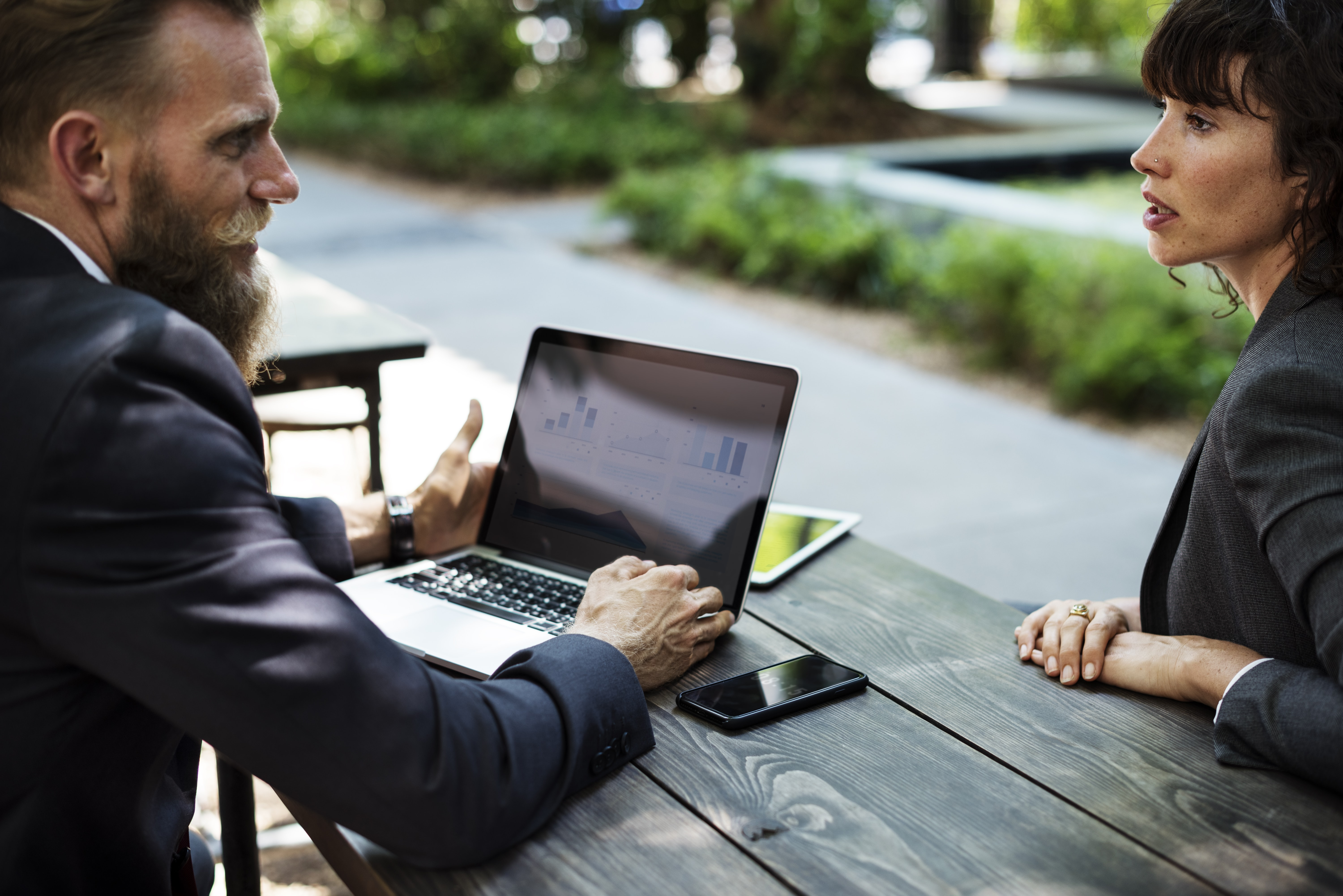man facing woman with laptop on table