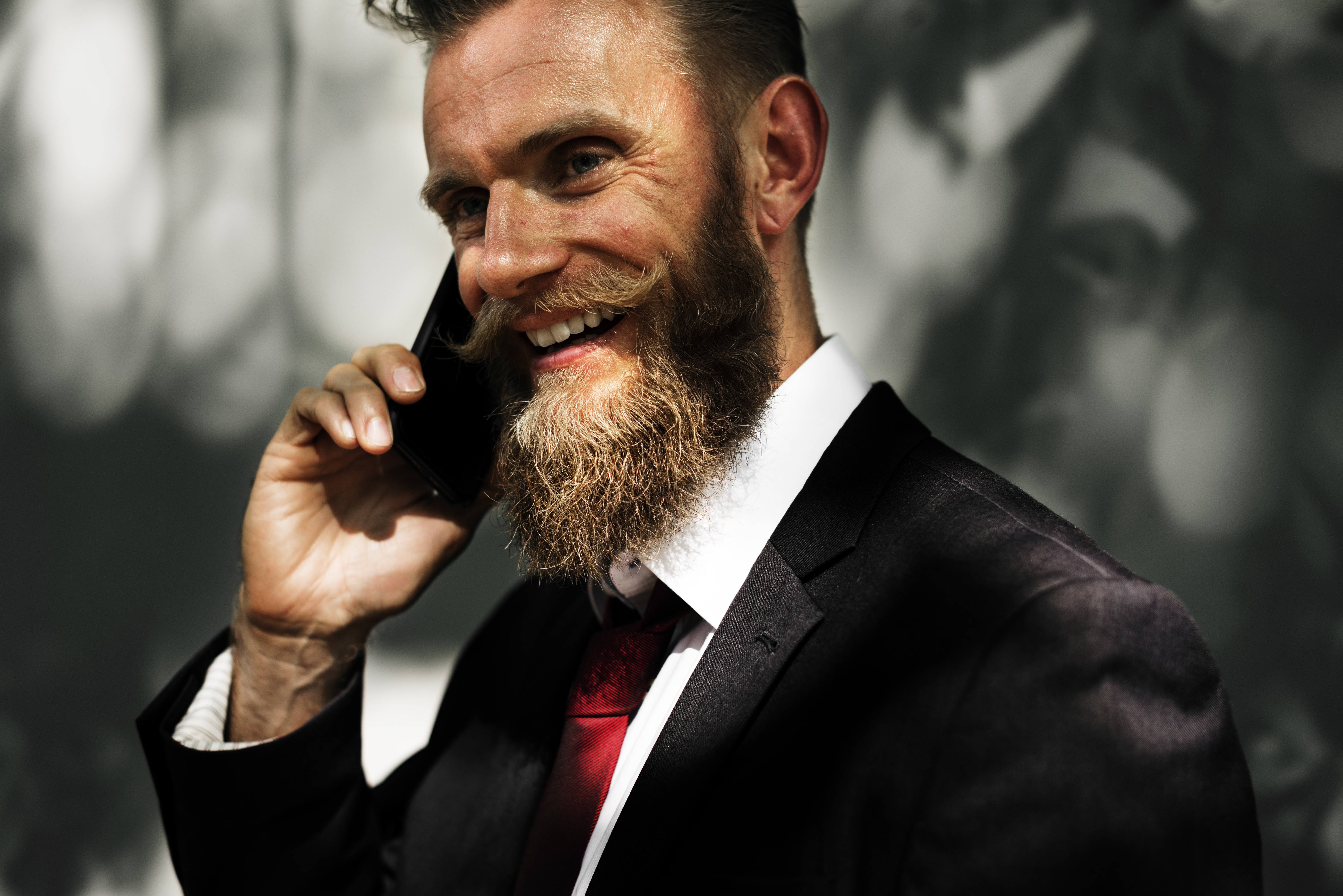 A bearded man in a black suit smiling while talking on a phone