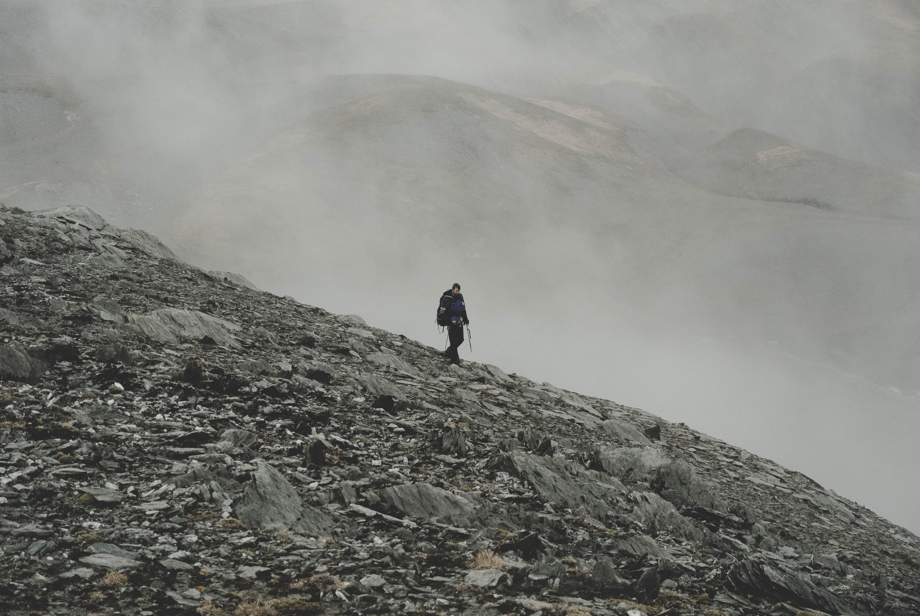 Hiker walks alone down a rocky slope in the fog
