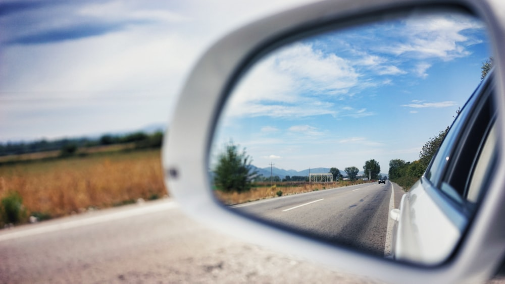 vehicle side mirror viewing car on the road during day