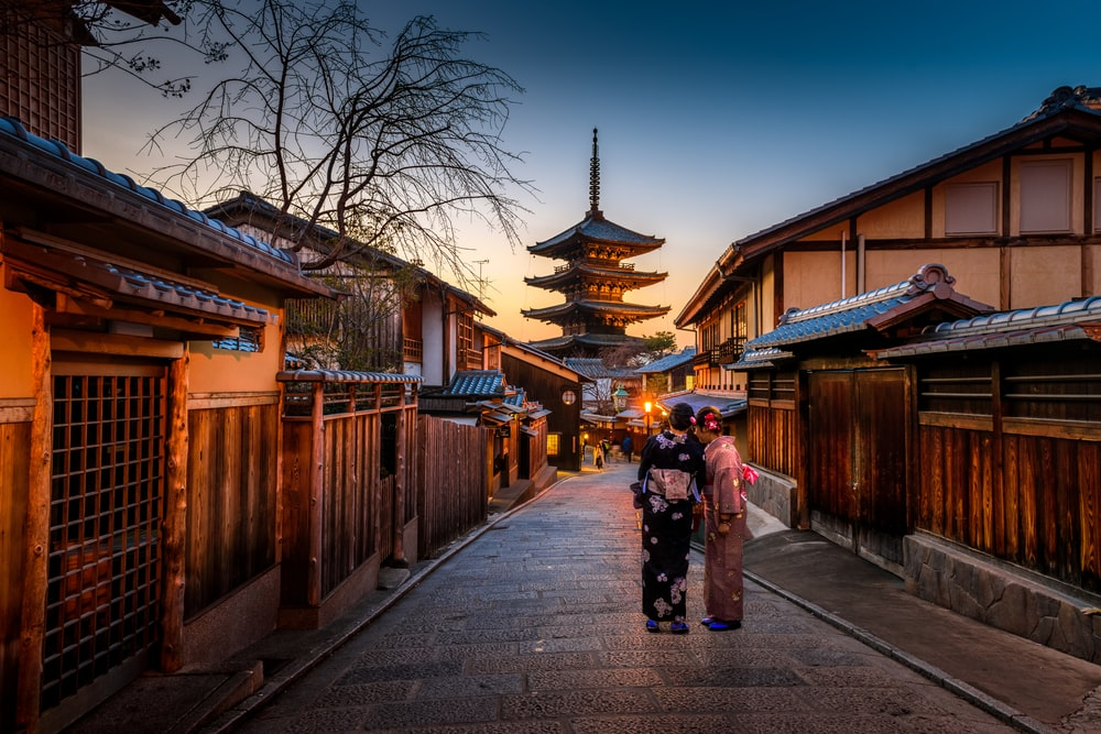two women in purple and pink kimono standing on street