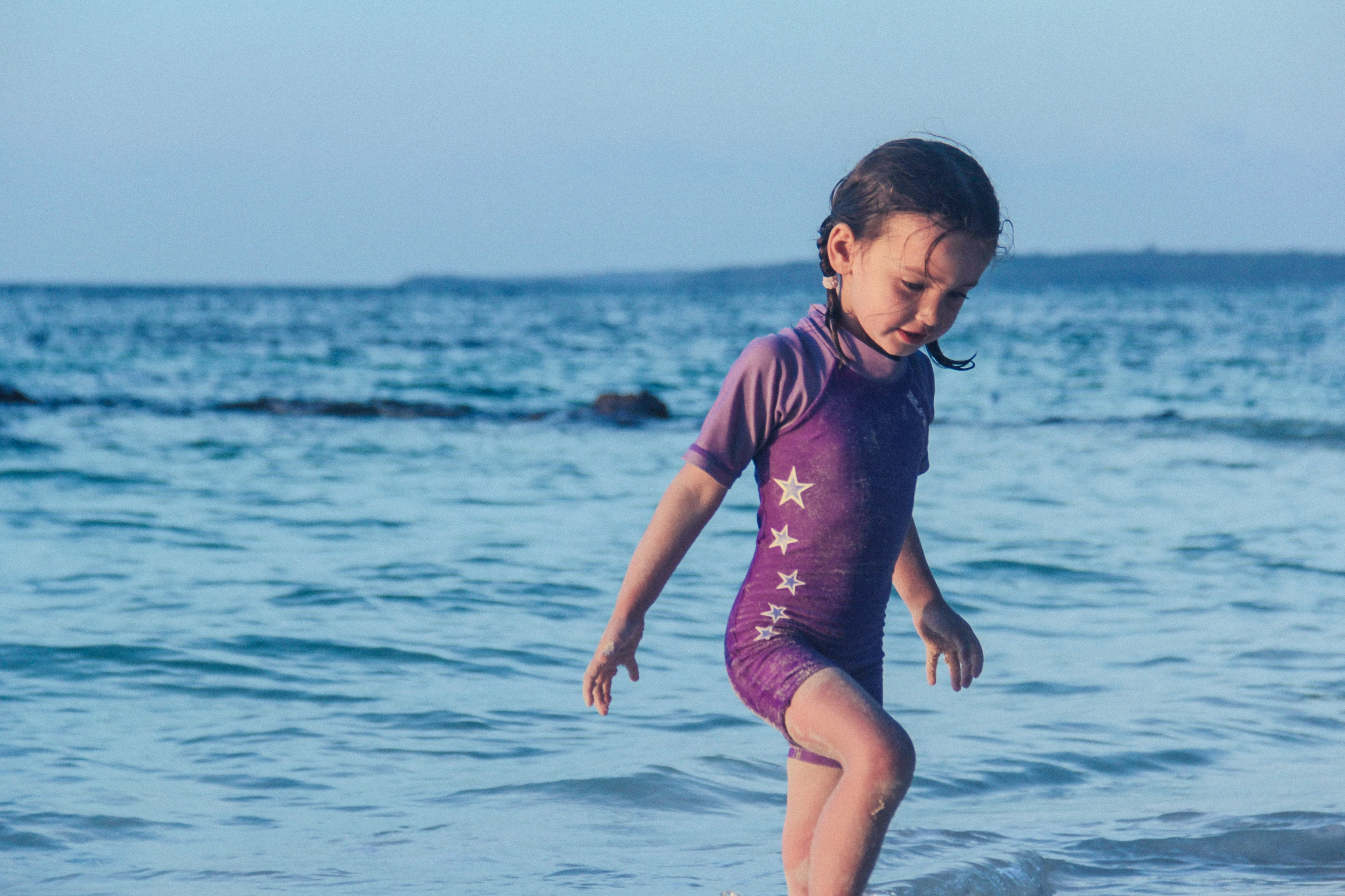 Female child in a purple swimsuit, covered in sand walking out of beach waters