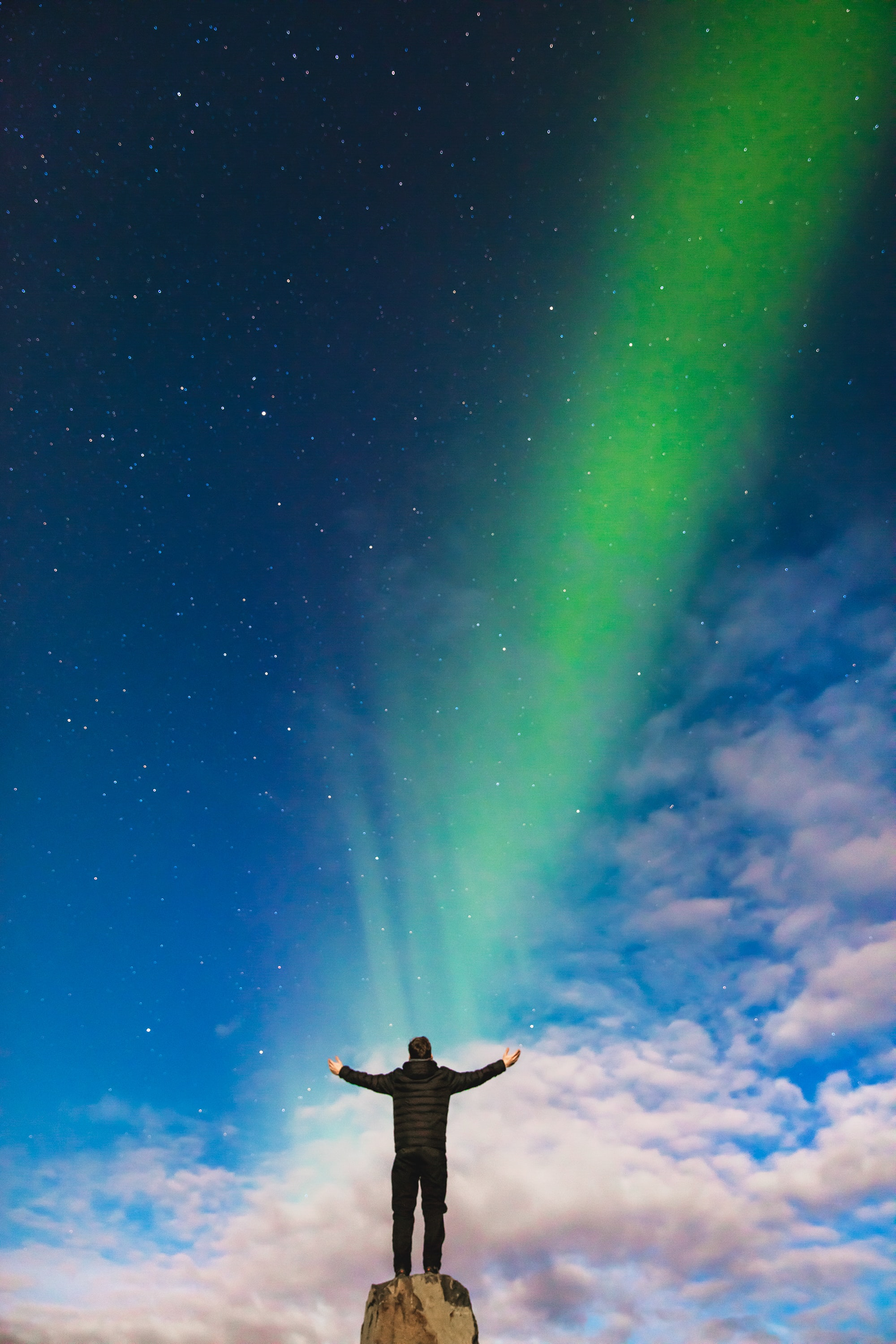 A man raising his arms on top of a rock formation while staring out at a Northern Lights beam in Iceland as it appears to shine onto him