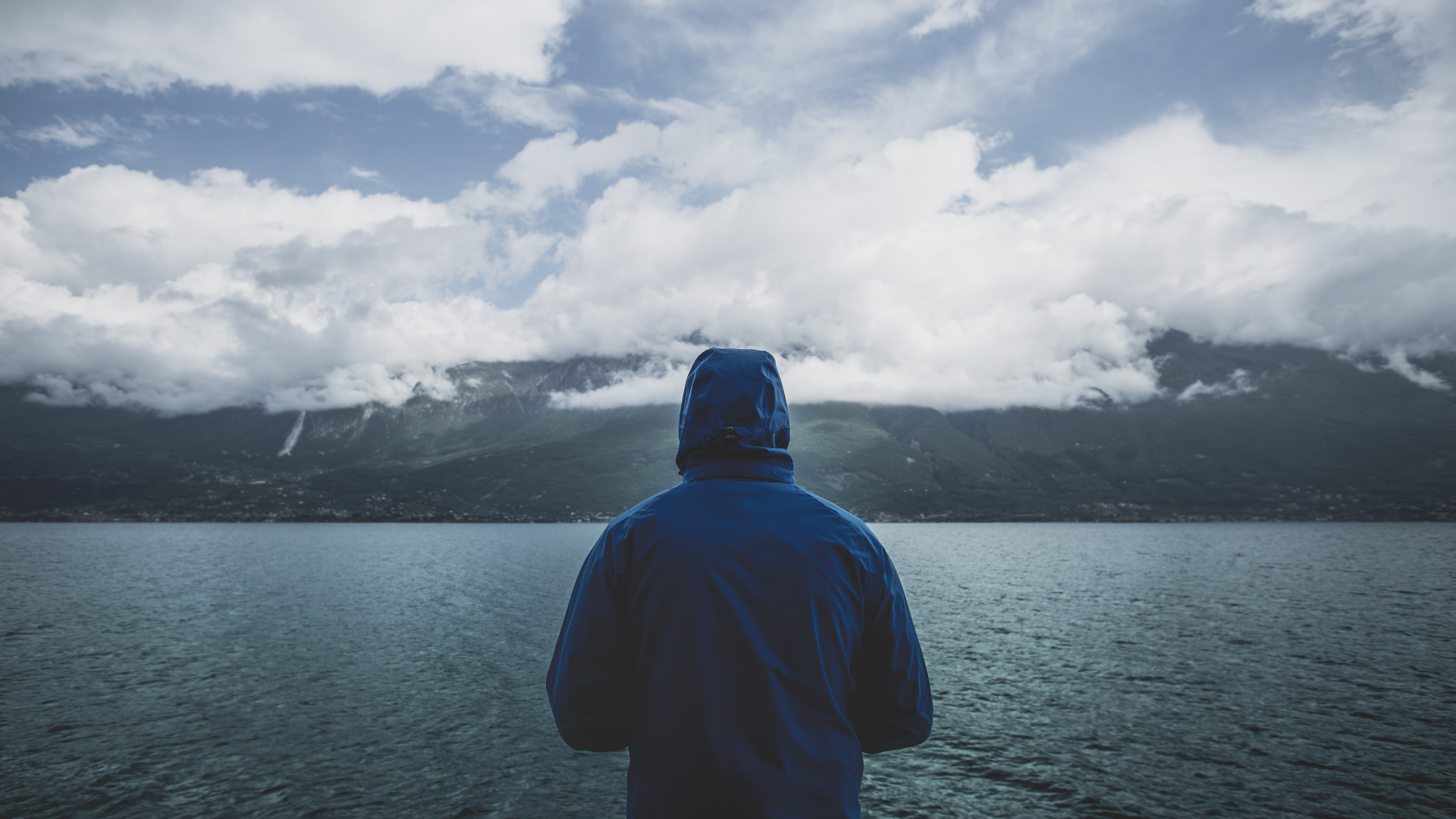 A man in a blue jacket staring out into a lake on a cloudy day