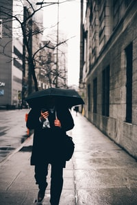 person holding black umbrella and walking in the street